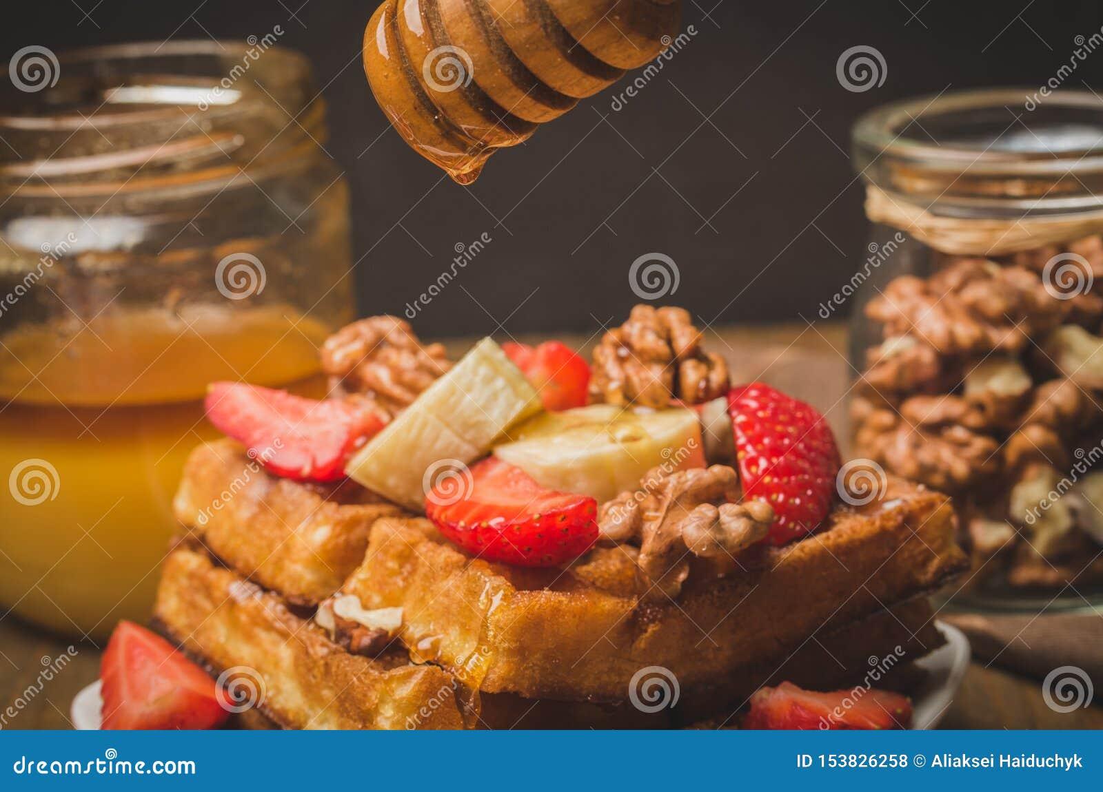 Honing die van honingsdipper op verfraaide wafeltjes, met aardbei, banaan en okkernoot druipen Sluit omhoog