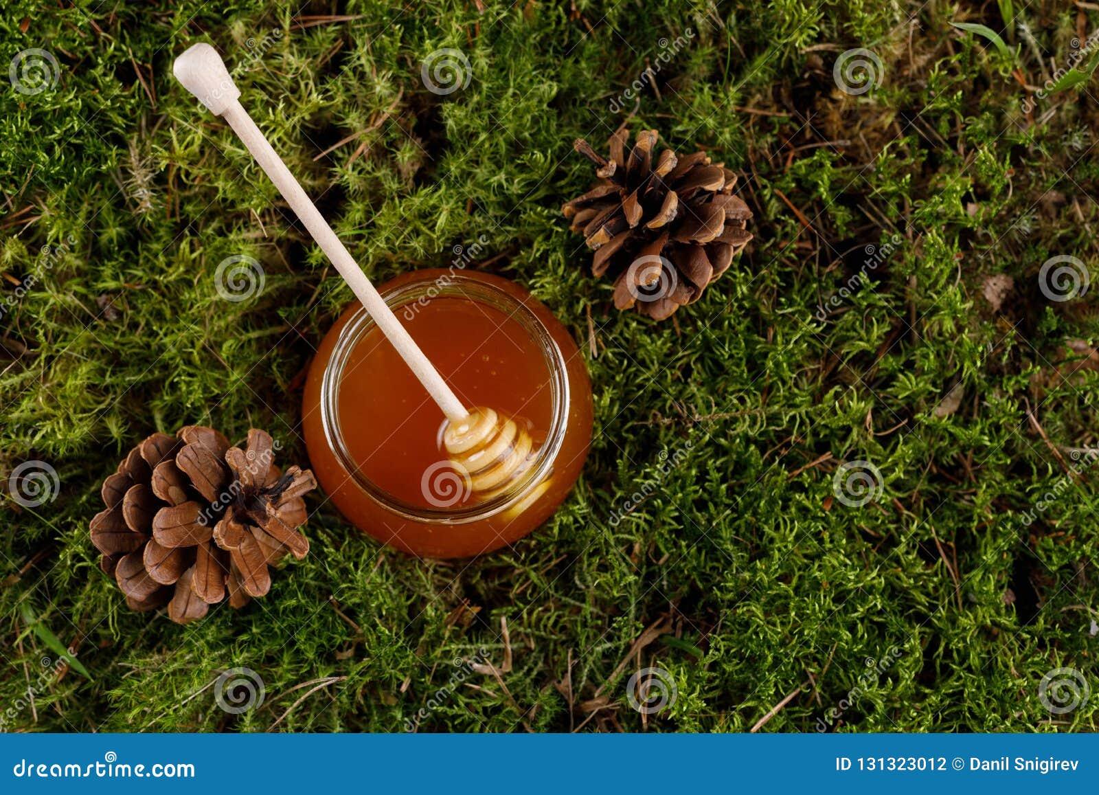 Honing in een glaskruik met een houten honingsstok op een achtergrond van bosmos