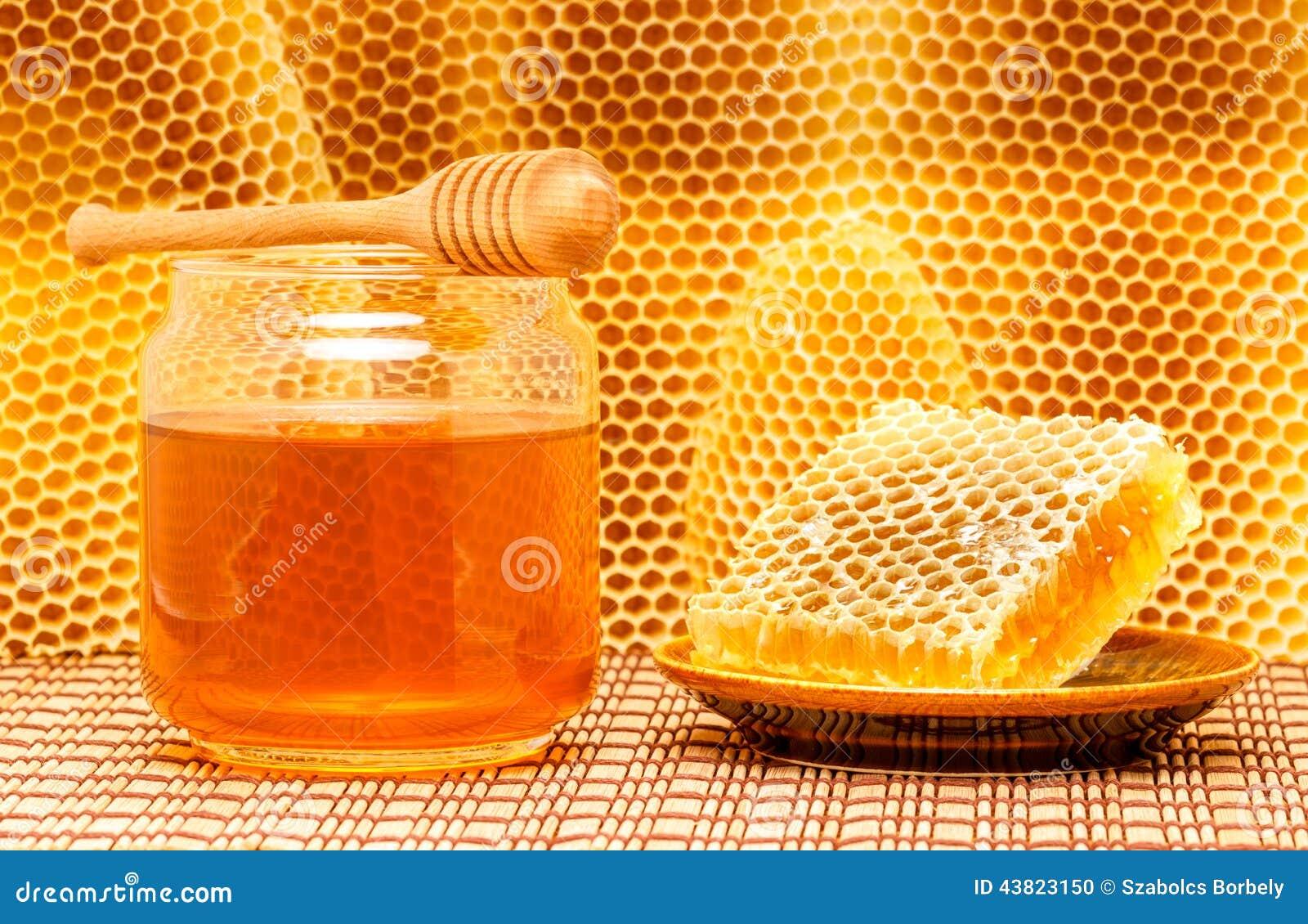 Honing in kruik met dipper en honingraat op mat