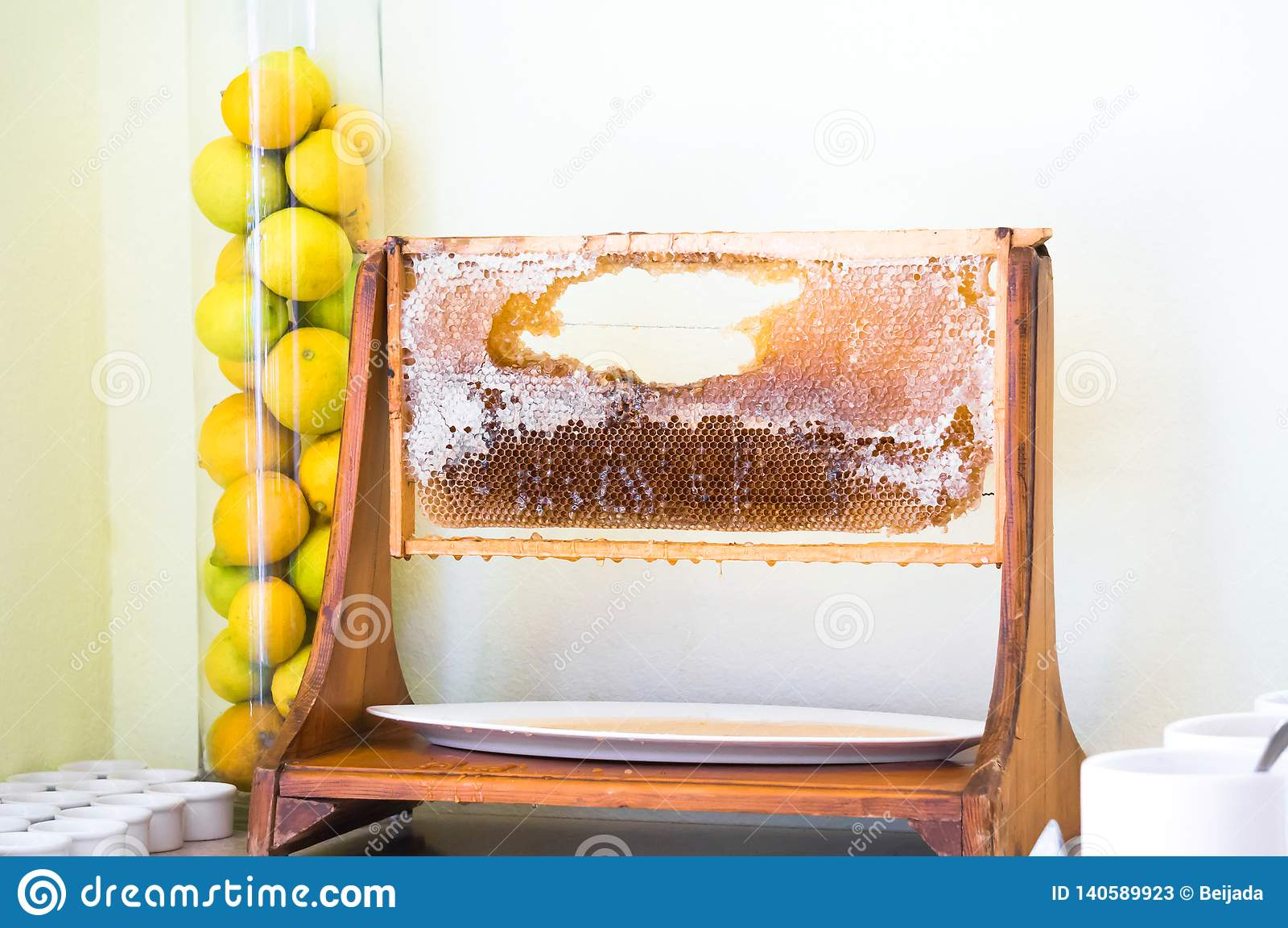 Honungskakaskärmram i restaurang och citroner åt sidan i vas för exponeringsglasrör