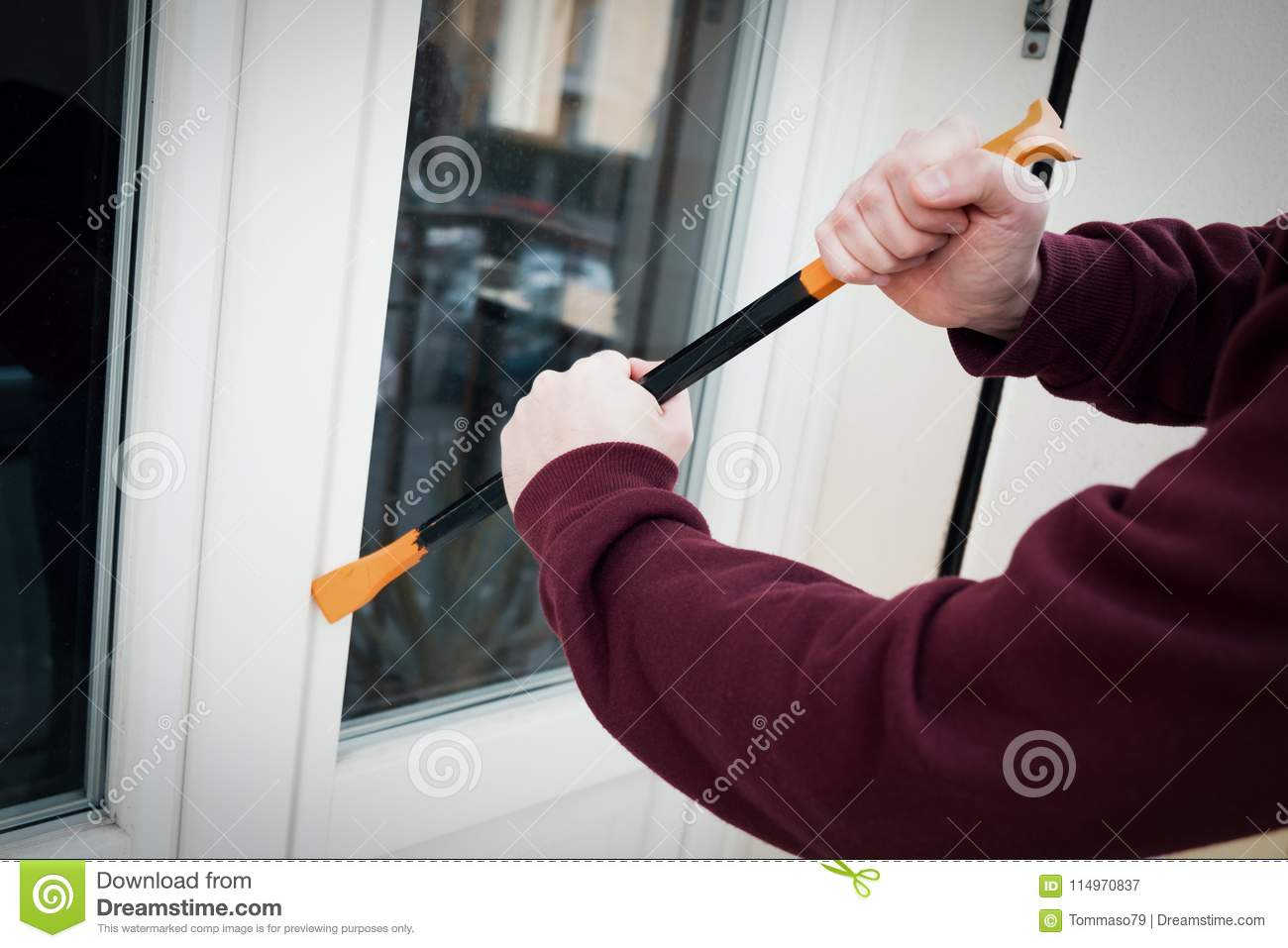 Hooded burglar forcing window lock to make a theft in a house