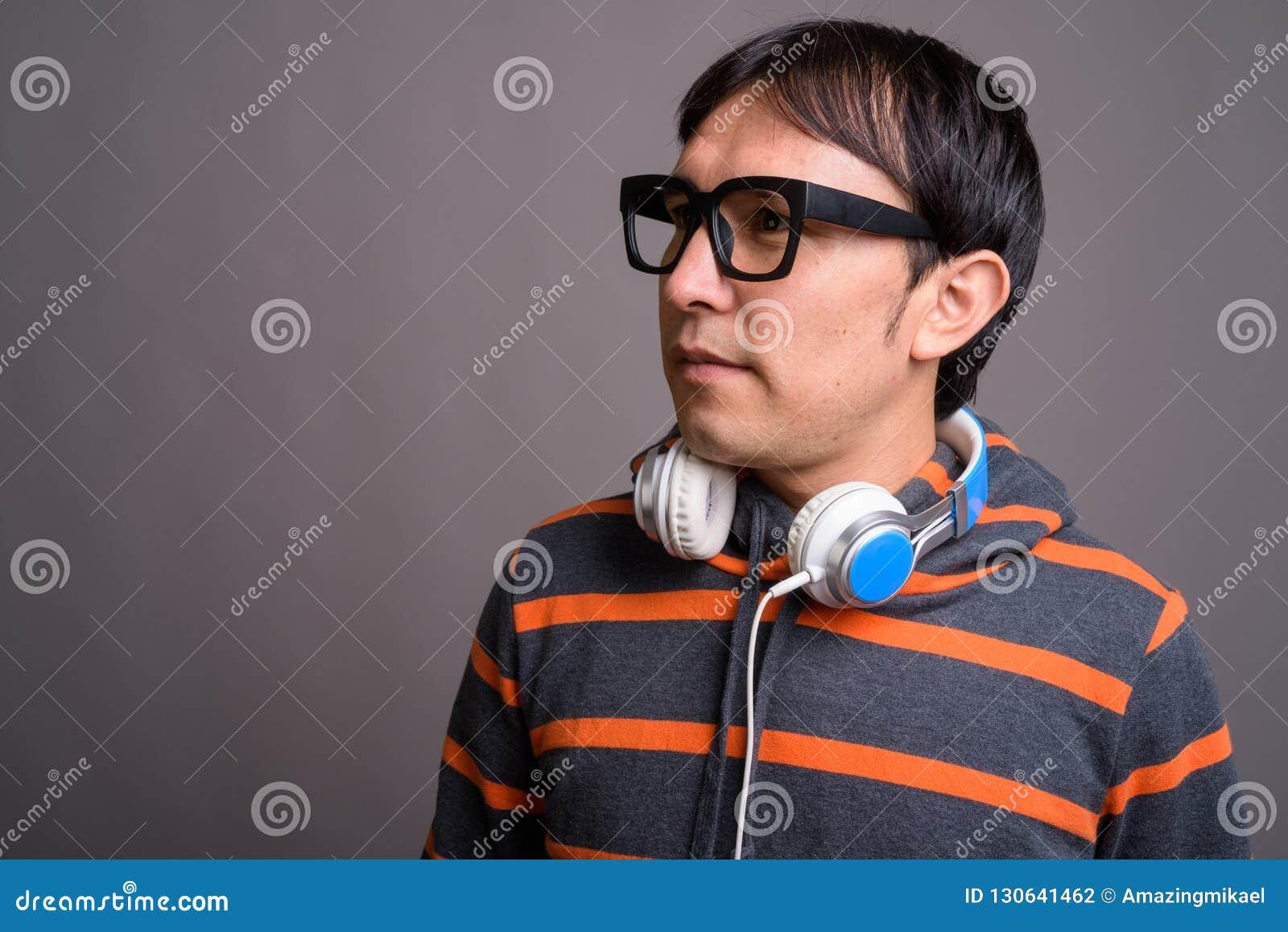 Hoodie och hörlurar för ung asiatisk nerdman bärande mot grå färger