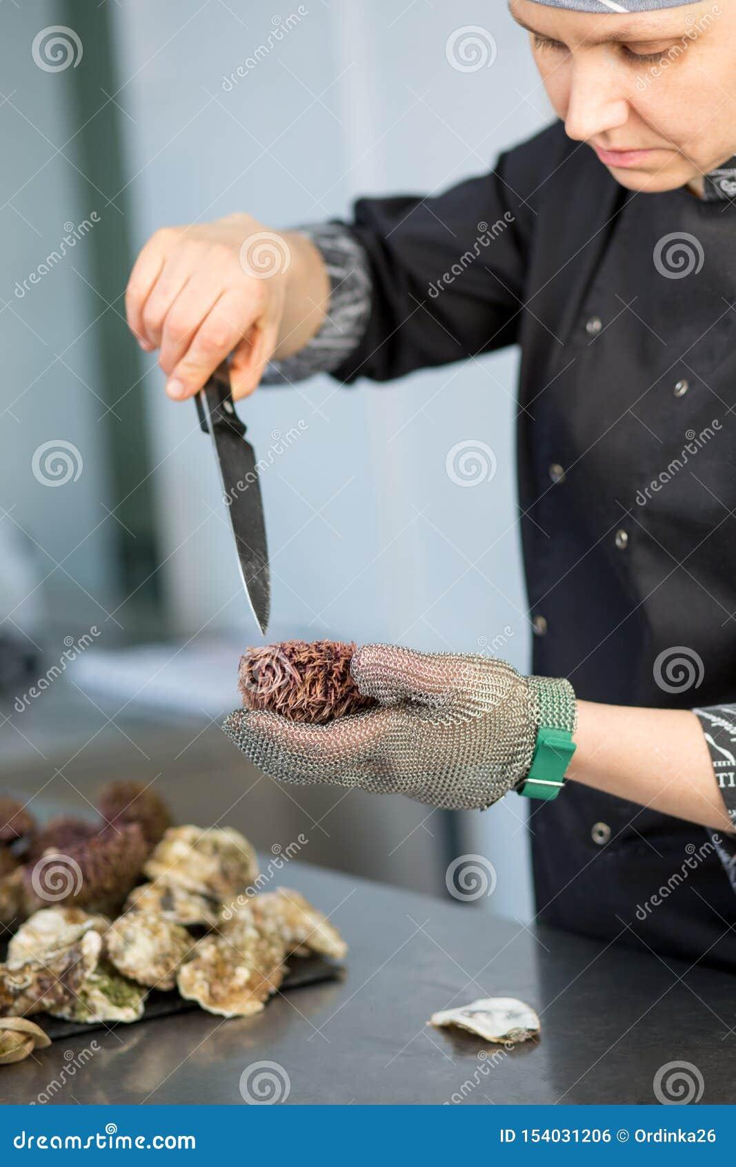 Hoofdklasse De chef-kok snijdt zeeëgel in de keuken van een restaurant Close-up van een hand met een mes in een metaalhandschoen