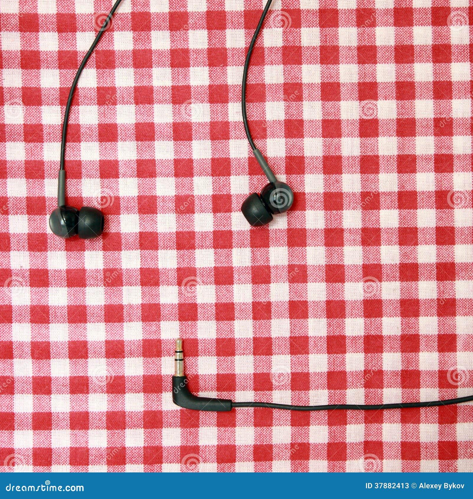 Hoofdtelefoons op een rood bedblad.