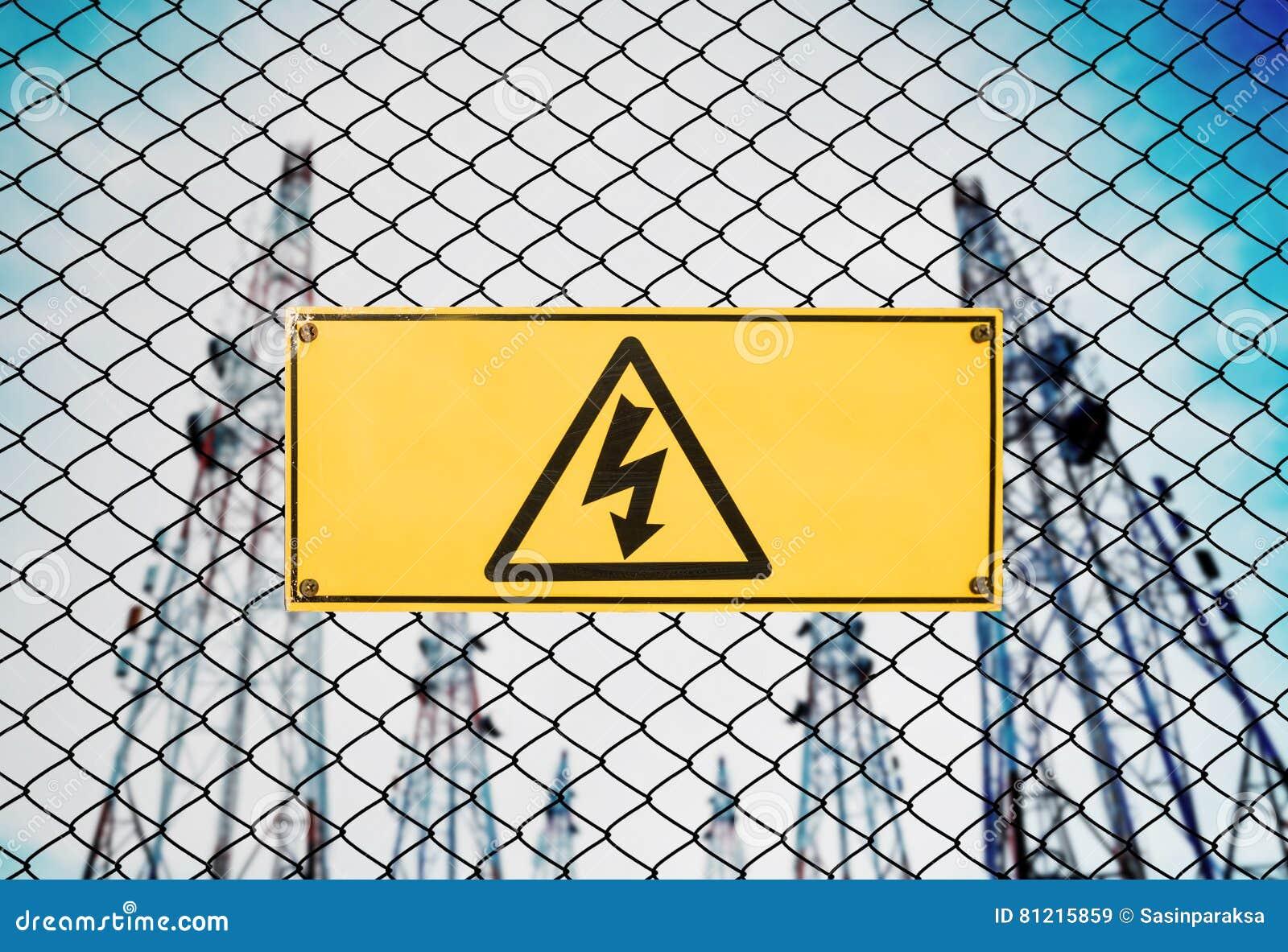 Hoogspanningsteken en het Uithangbord van de Symboolvoorzichtigheid op Omheining Wire bij Elektroelektrische centralepost