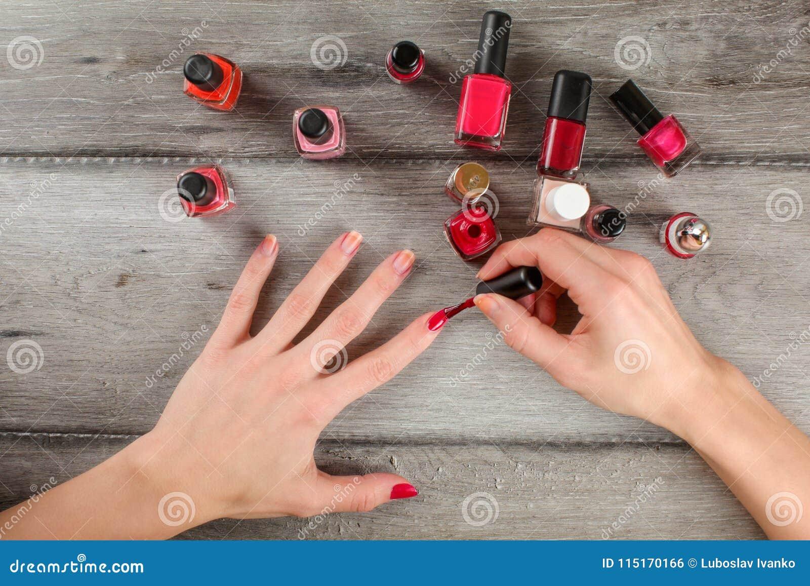 Hoogste mening aan vrouwenhanden, die laag van rode spijkervernis toepassen op hij
