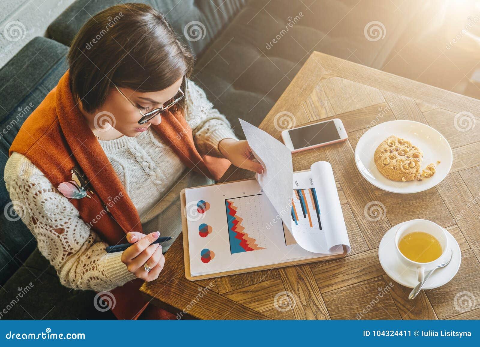 Hoogste mening De jonge aantrekkelijke vrouw, ondernemer zit in koffie bij lijst en het werken De onderneemster bekijkt grafieken