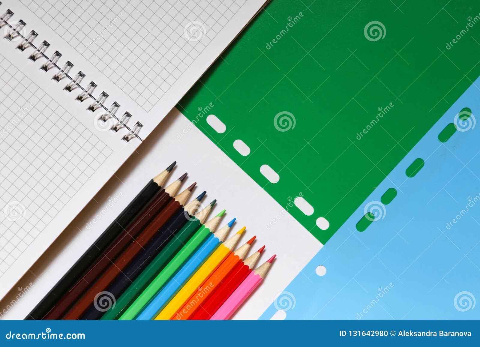 Hoogste mening over notitieboekjes, potloden, op een groenachtig blauwe achtergrond Terug naar het Concept van de School