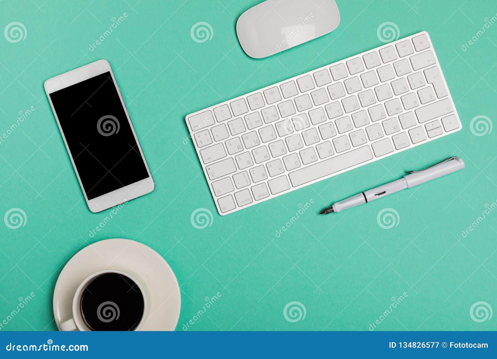 Hoogste mening van bureauwerkruimte met smartphone, toetsenbord, koffie en muis op blauwe achtergrond met exemplaar ruimte, grafi
