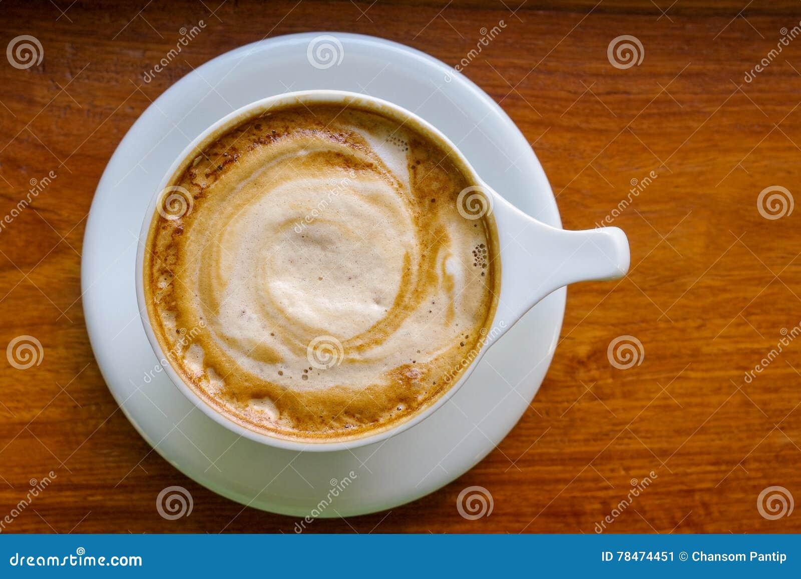 Hoogste mening van de kop van de cappuccinokoffie met melkschuim op houten backgro
