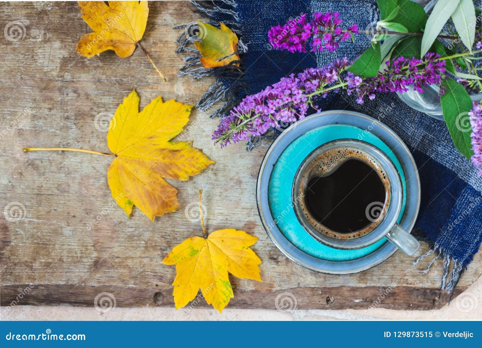 Hoogste mening van een blauwe kop koffie, blauwe geruite sjaal, purpere bloemen in een vaas en gouden bladeren op houten achtergr