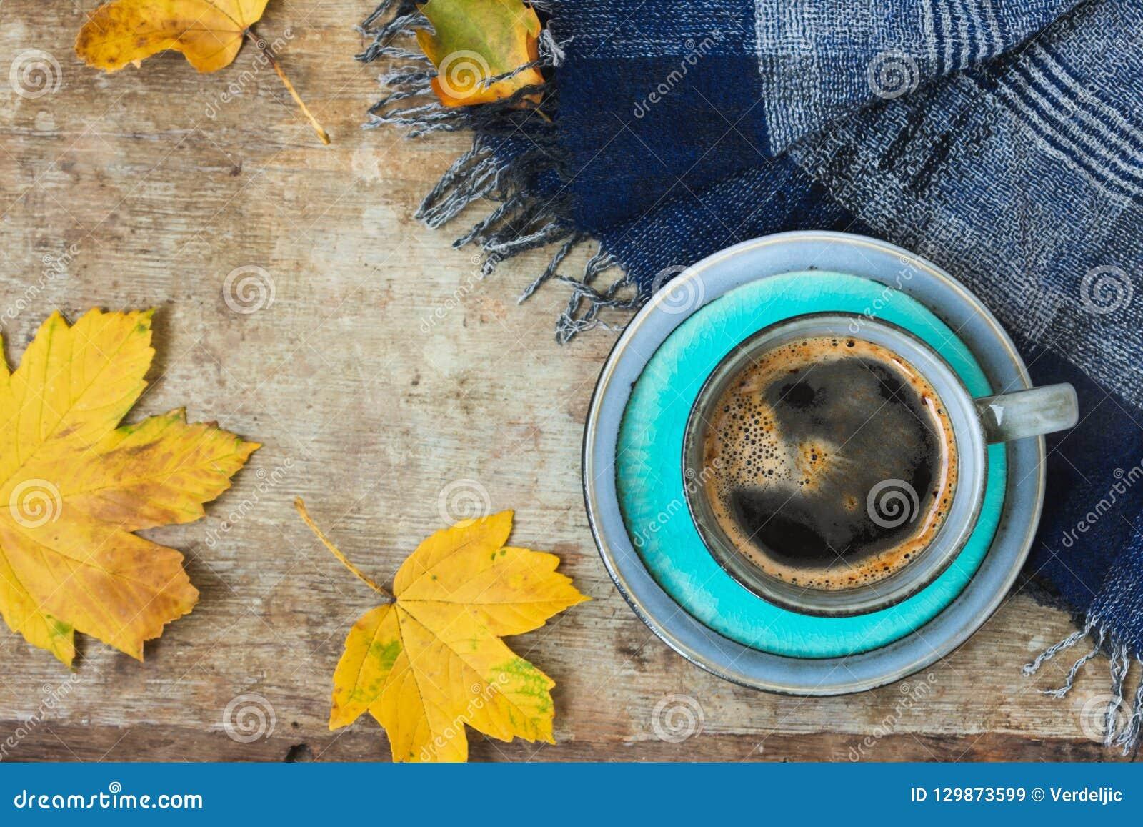 Hoogste mening van een blauwe kop koffie, blauwe sjaal en gouden bladeren op houten achtergrond