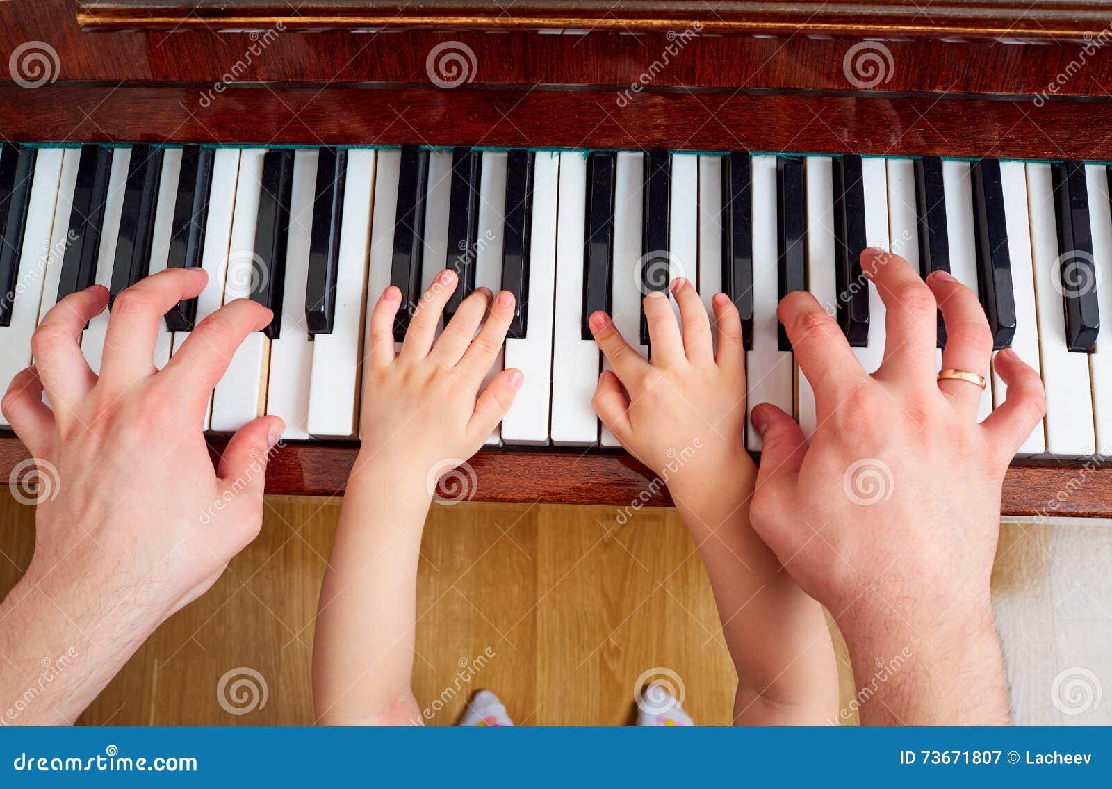 Hoogste mening van een hand, een toetsenbord van de kindpiano De hand o van het kleine kind