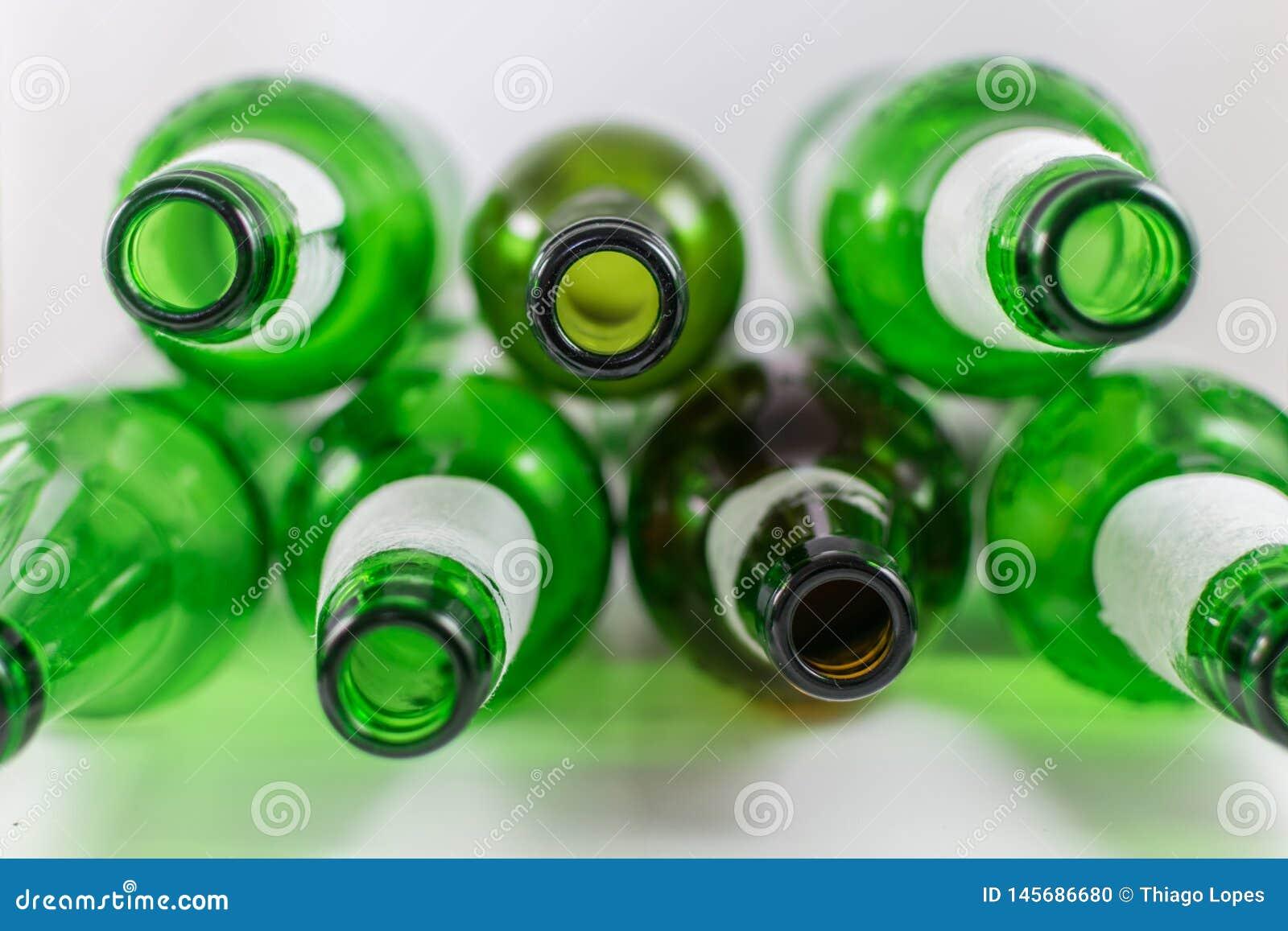 Hoogste mening van een pak lege bier en wijn groene en bruine glasflessen, met gescheurde etiketten op een witte achtergrond herg