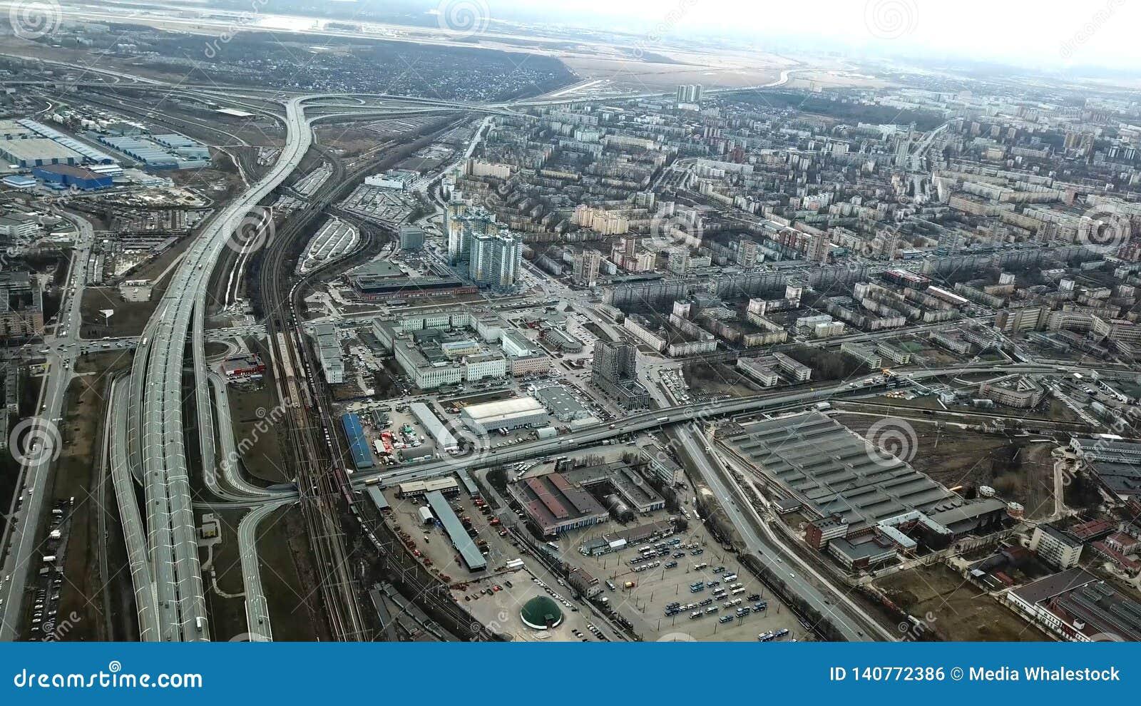 Hoogste mening van grijze metropool Panorama van grote stad met gebieden en het overgaan van lange weg in bewolkt weer suburban