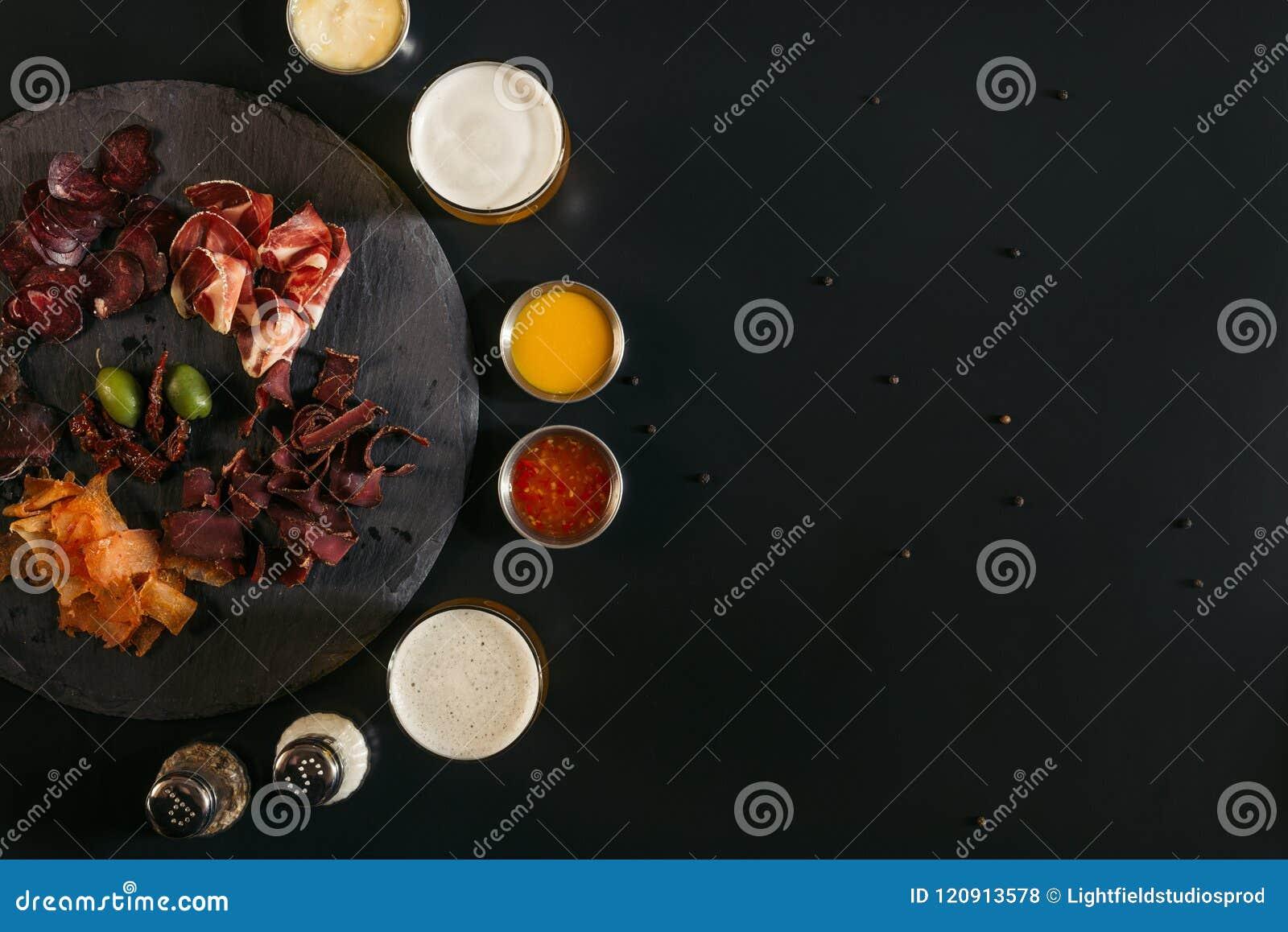 Hoogste mening van heerlijk gesneden geassorteerd vlees, glazen bier, sausen en kruiden