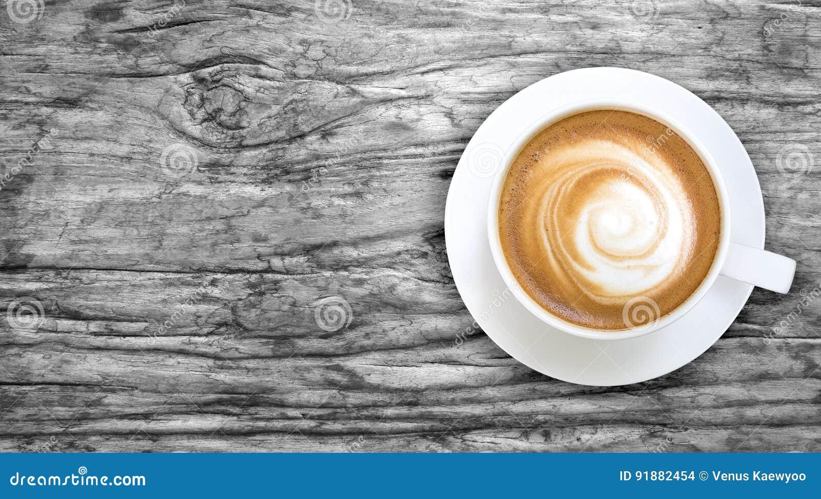 Hoogste mening van hete koffiecappuccino in een witte ceramische kop op grijs