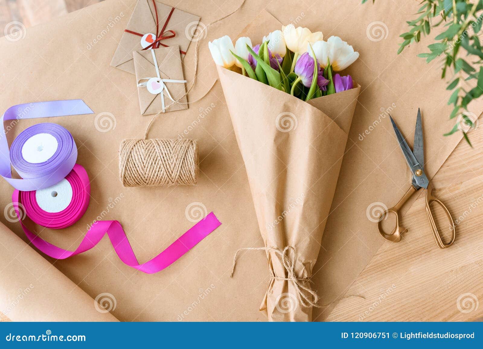 Hoogste mening van mooi boeket van tulpen, schaar, linten en enveloppen met kabel