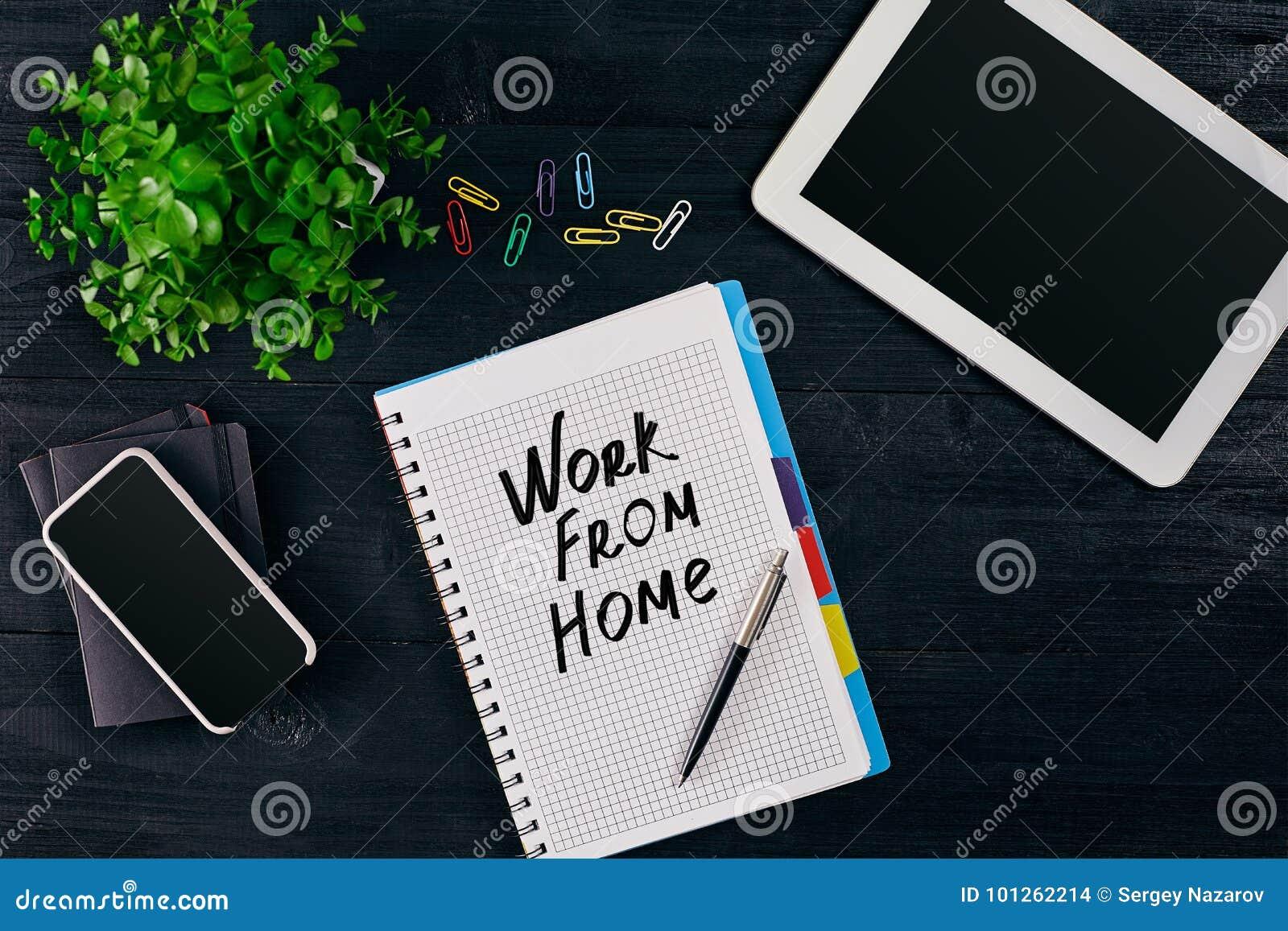 Hoogste mening van open die notitieboekje met het WERK VAN HUISinschrijving wordt geschreven Groene bloem, tablet, gekleurde slim
