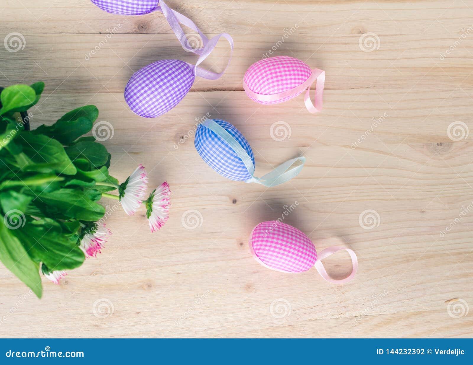 Hoogste mening van roze en blauwe geruite paaseierendecoratie en witte en roze madeliefjes op bleke houten achtergrond