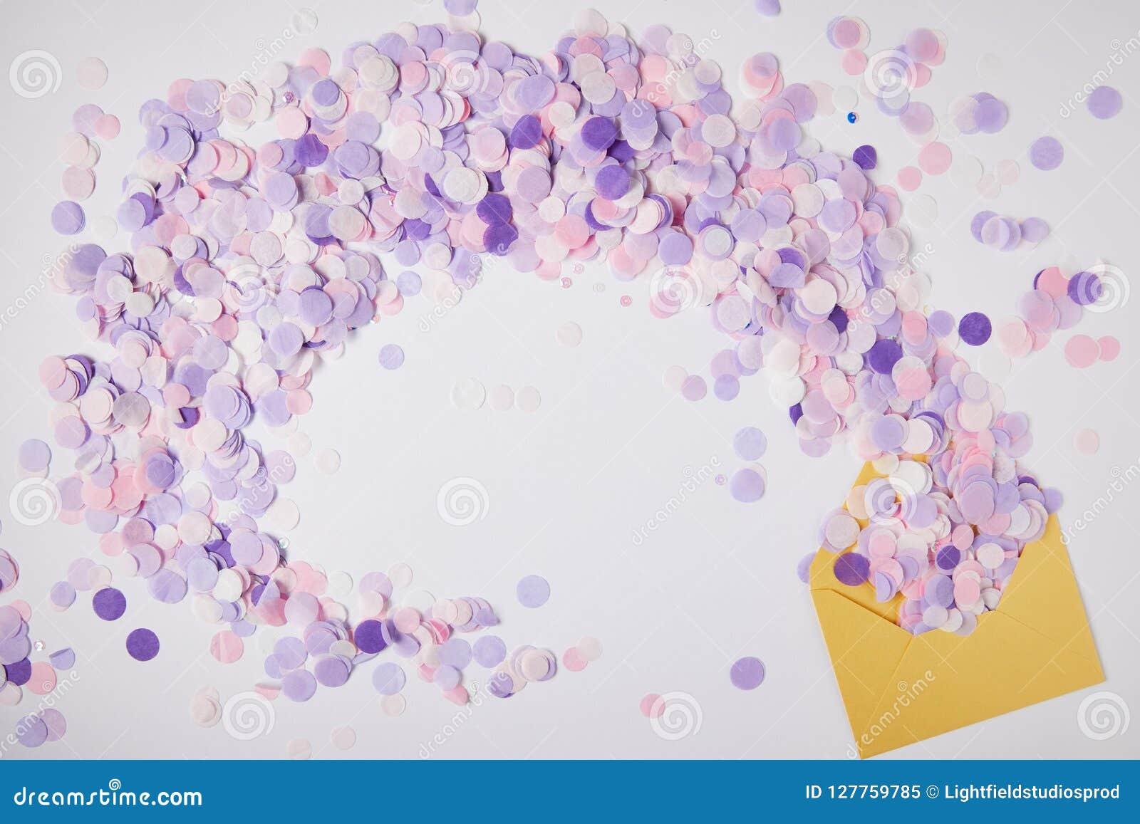 Hoogste mening van violette confettienstukken en gele envelop op oppervlakte