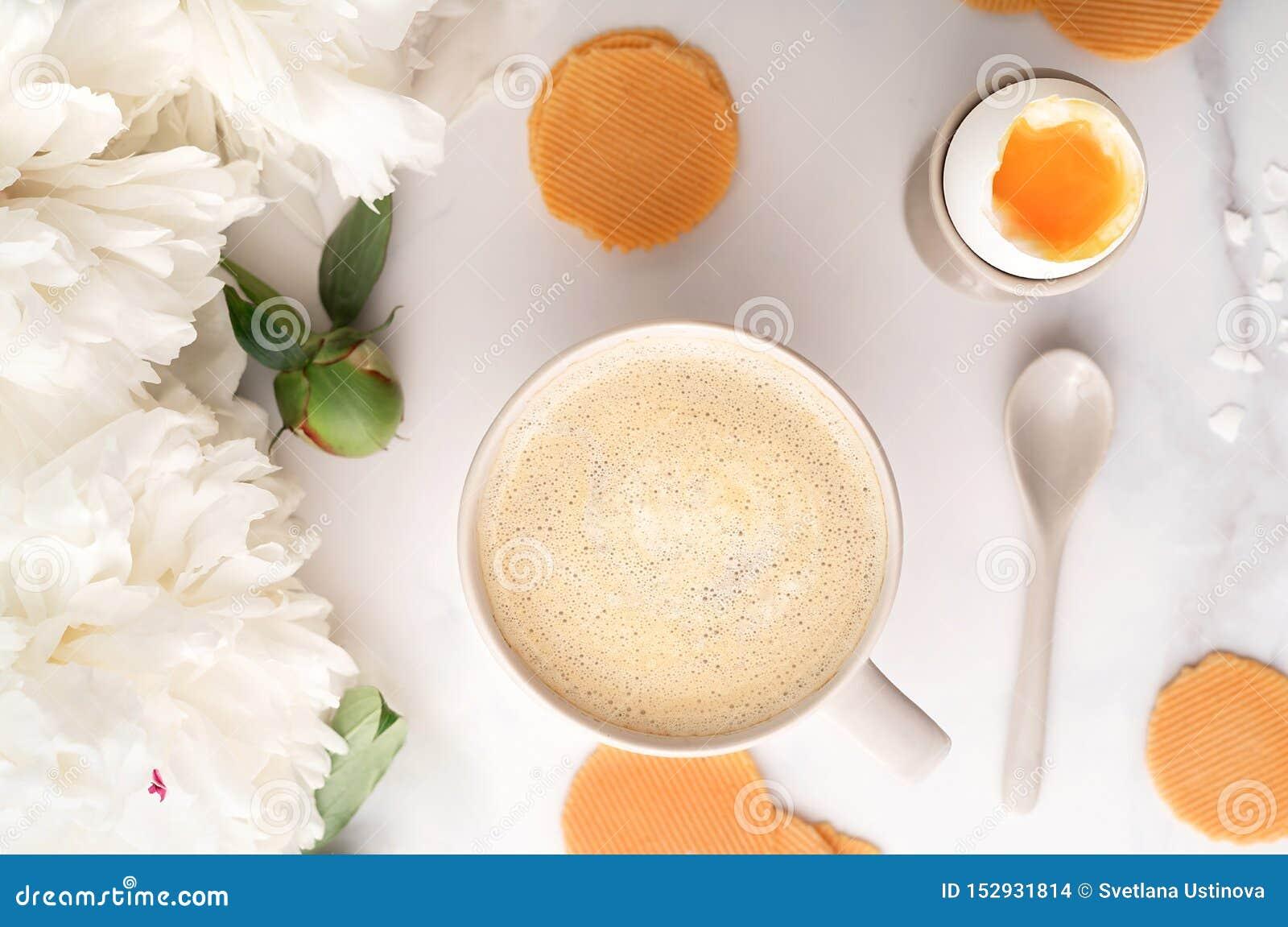 Hoogste mening van zacht-gekookt ei met liquide oranje dooier in ceramisch eierdopje, kop van koffie, dunne knapperige graanspaan