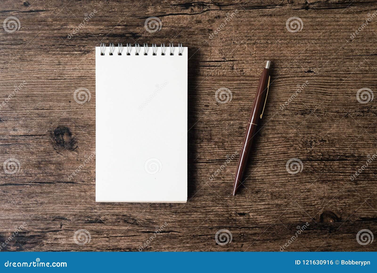 Hoogste meningsbeeld van open notitieboekje met blanco pagina en pen op w