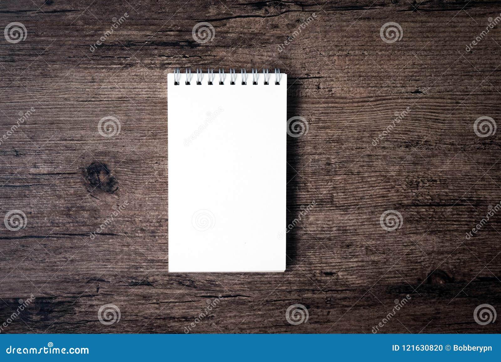 Hoogste meningsbeeld van open notitieboekje met blanco pagina op houten Ta
