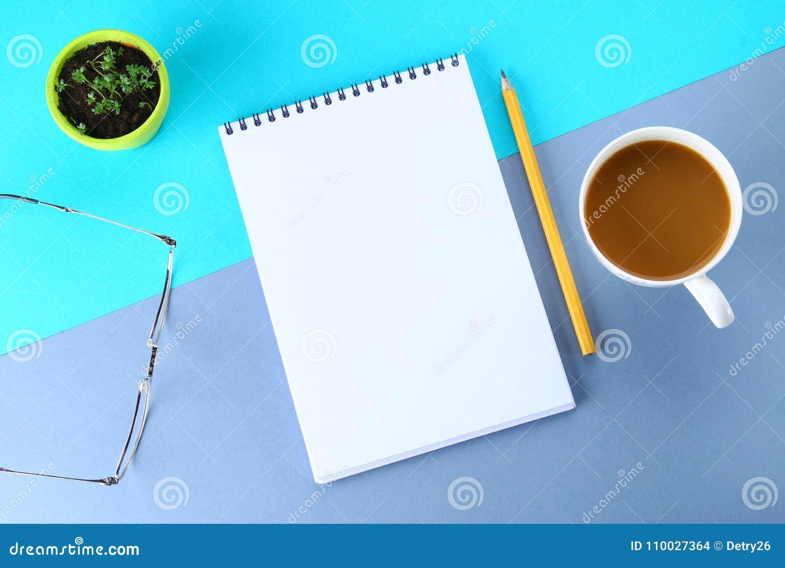 Hoogste meningsbeeld van open notitieboekje met blanco pagina s en koffie op blauwe achtergrond, klaar voor het kloppen of spot S