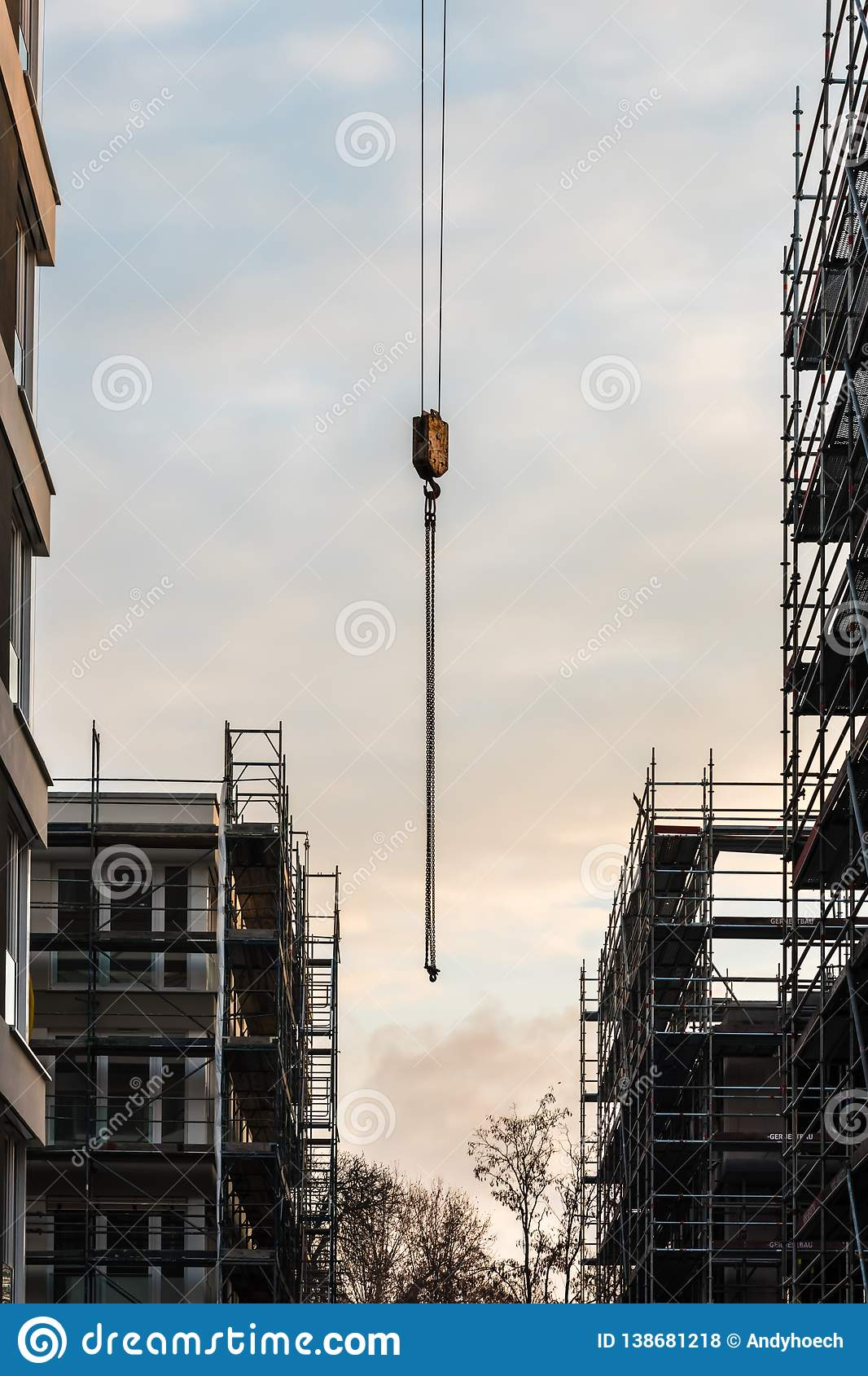 The hook of the crane between the new house and the scaffolding