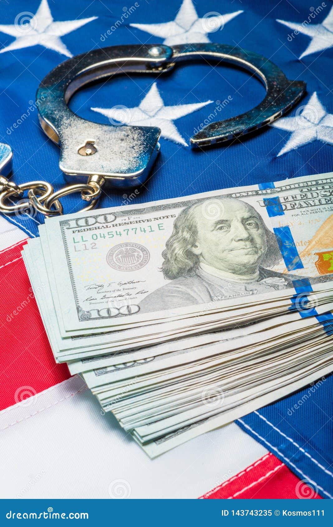 Hoop van geld en handcuffs op Amerikaanse vlag dichte omhooggaand