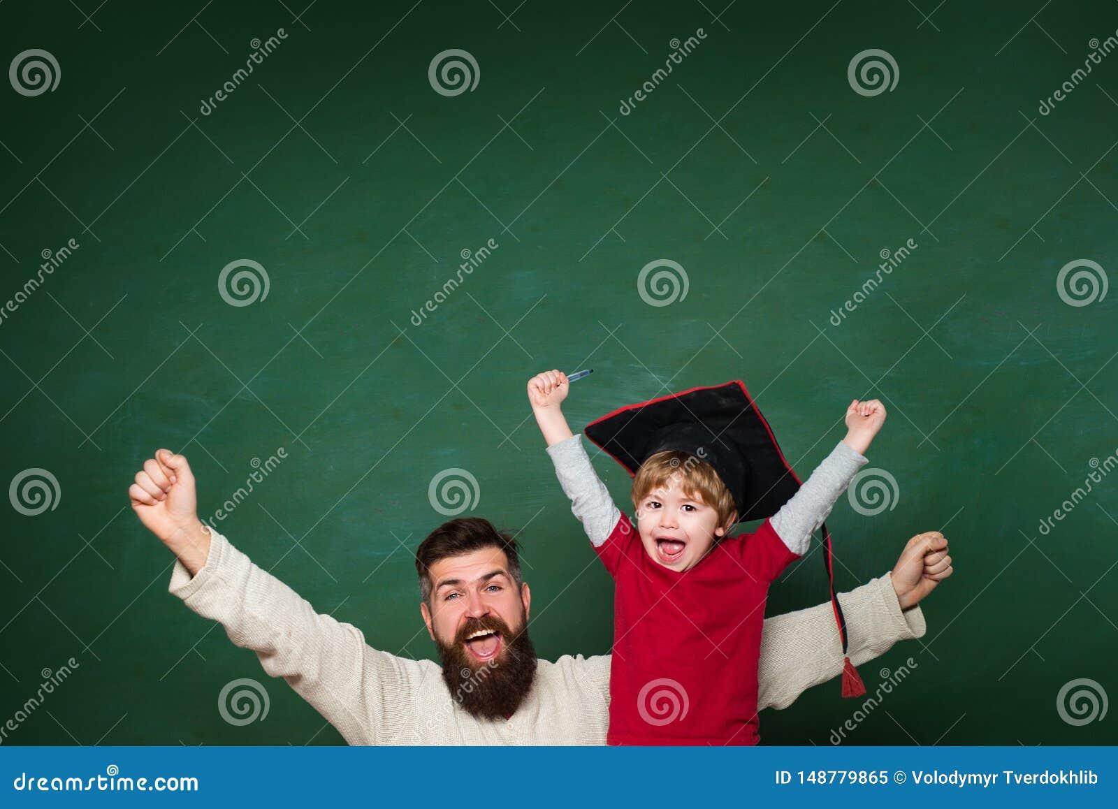 Hooray Vader die haar zoon in klaslokaal onderwijzen op school Twee generaties Jonge jongen die zijn schoolthuiswerk met van hem