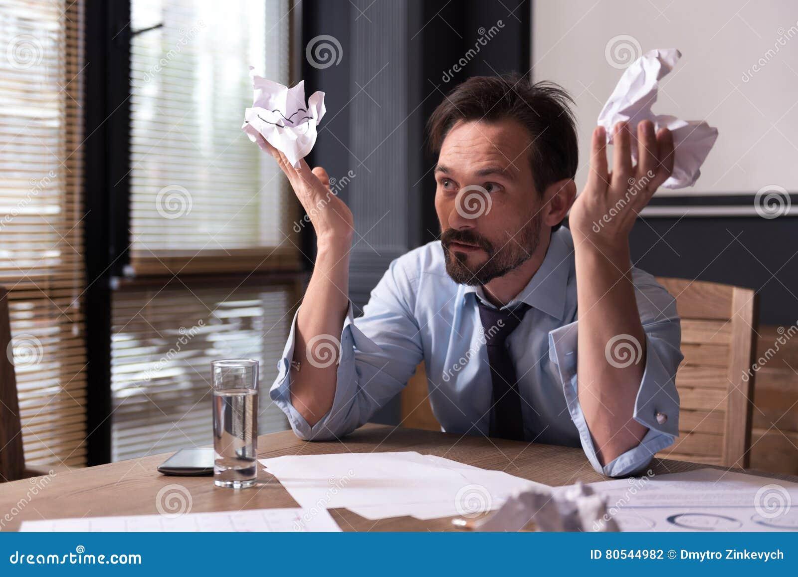 Hopeless miserable man holding crumpled paper