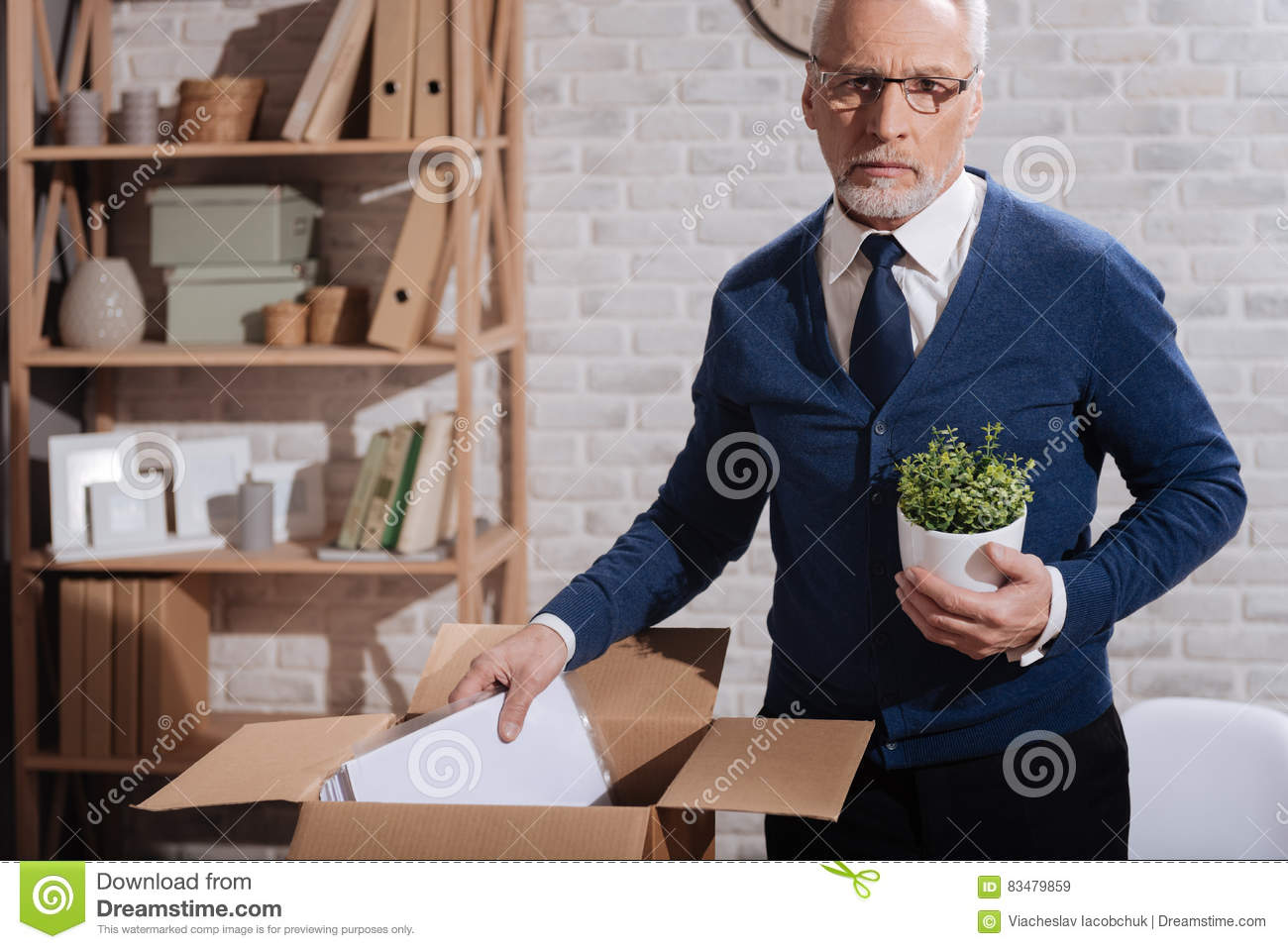 Hopeless professional clearing his workplace