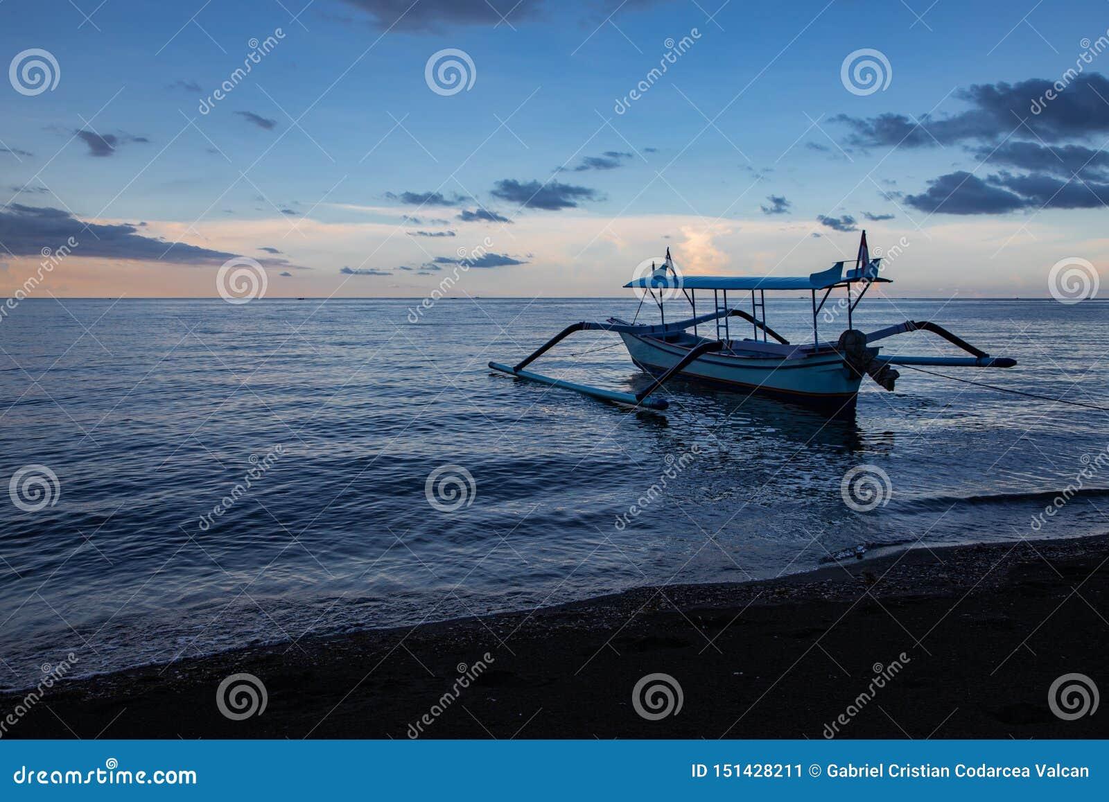 Hora azul sobre o oceano calmo e a praia preta da areia com barco do balinese