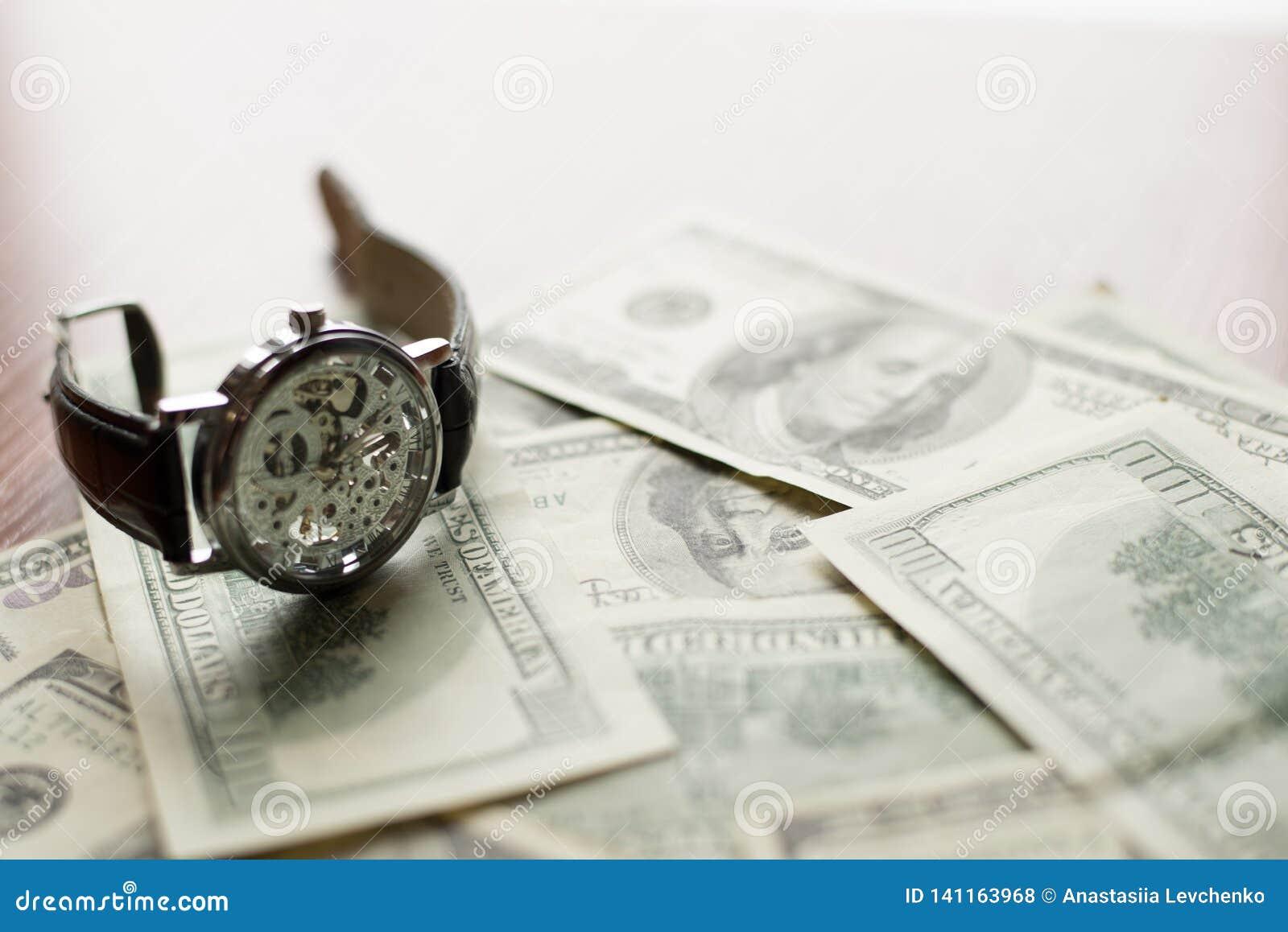 Hora de pagar - 100 dólares de billete de banco y el reloj clásico con los números romanos