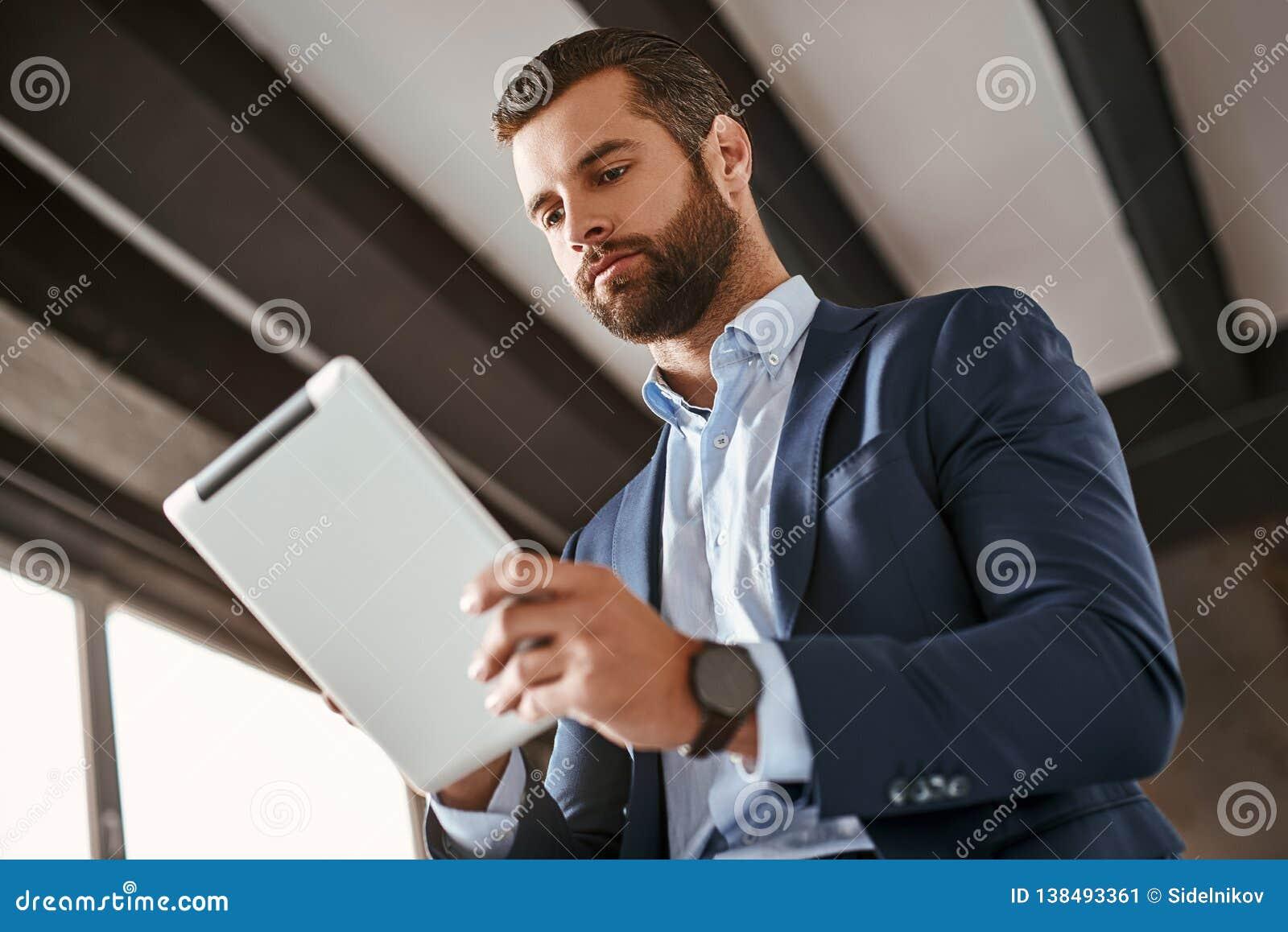 Hora de trabalhar! O homem de negócios novo farpado seguro no terno à moda está usando a tabuleta digital