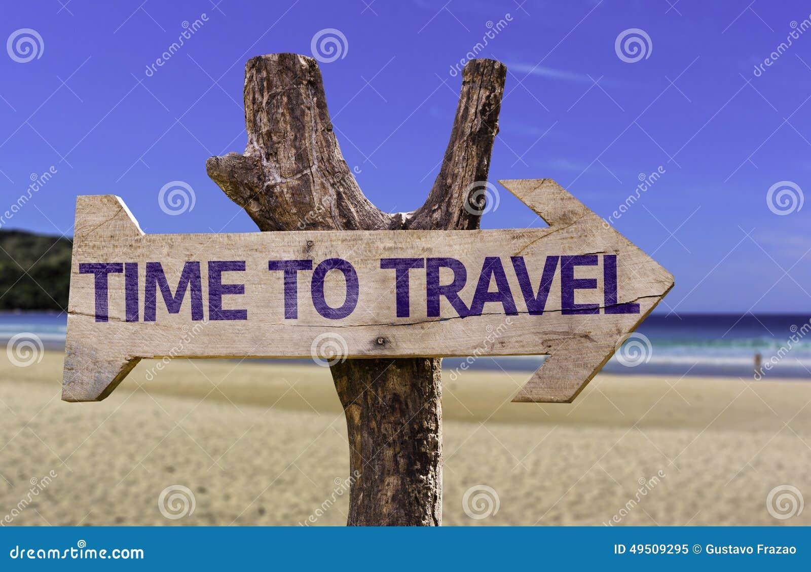 Hora de viajar sinal de madeira com uma praia no fundo