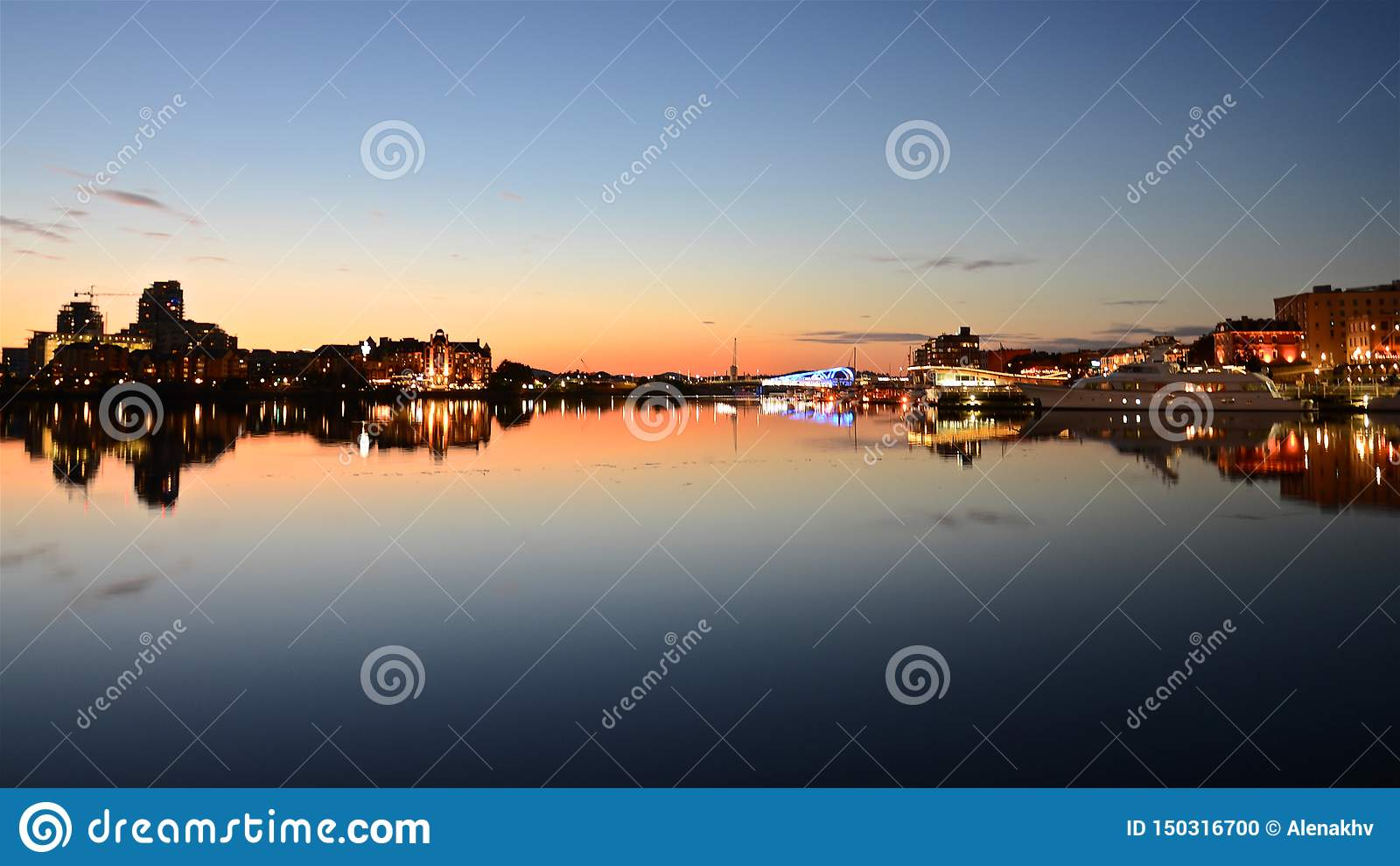 Horisont med de ljusa aftonljusen av Victoria City och solnedgångstrålar ljus bildar en spegelbild på vattnet av fjärden
