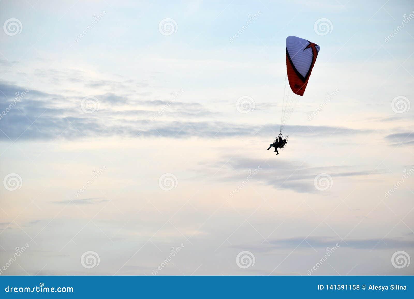 Horisontalfoto av flyget av två personer på en paraglider i molnig himmel för frikänd en litet i sommaren