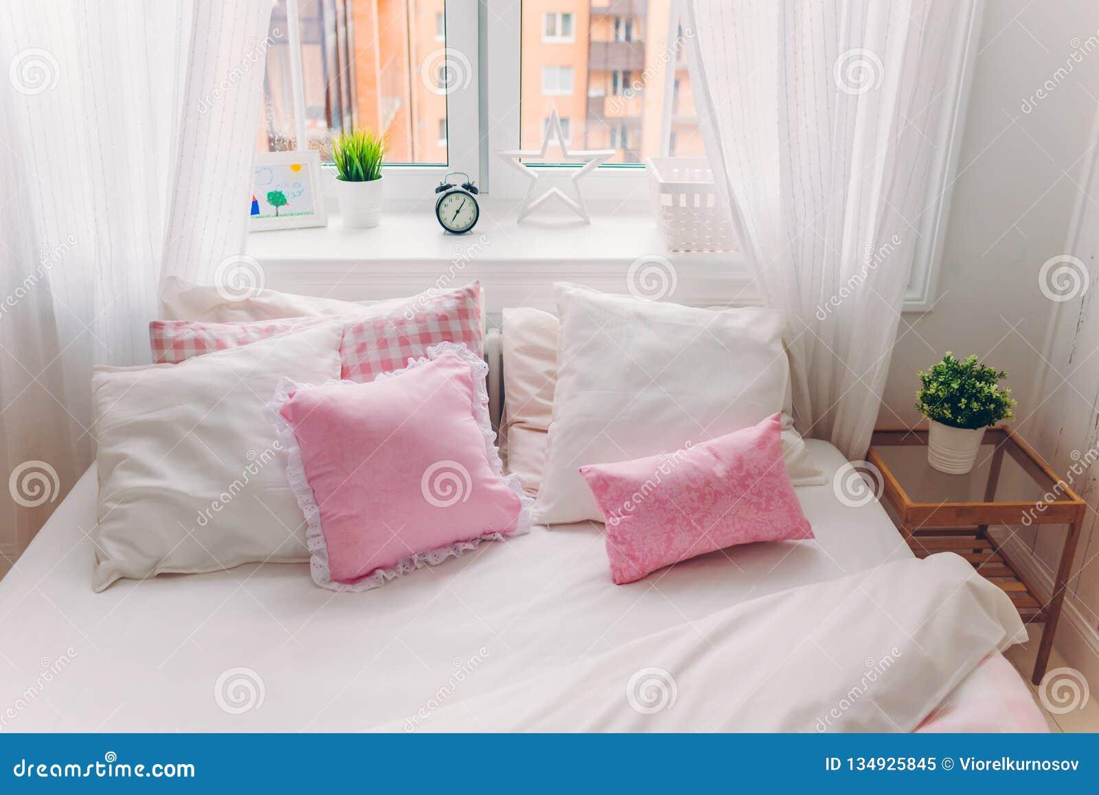 Horisontalskott av säng med vit sängkläder, mjuka kuddar, fönstret med den gröna växten, ringklockan och bilden, inga personer co