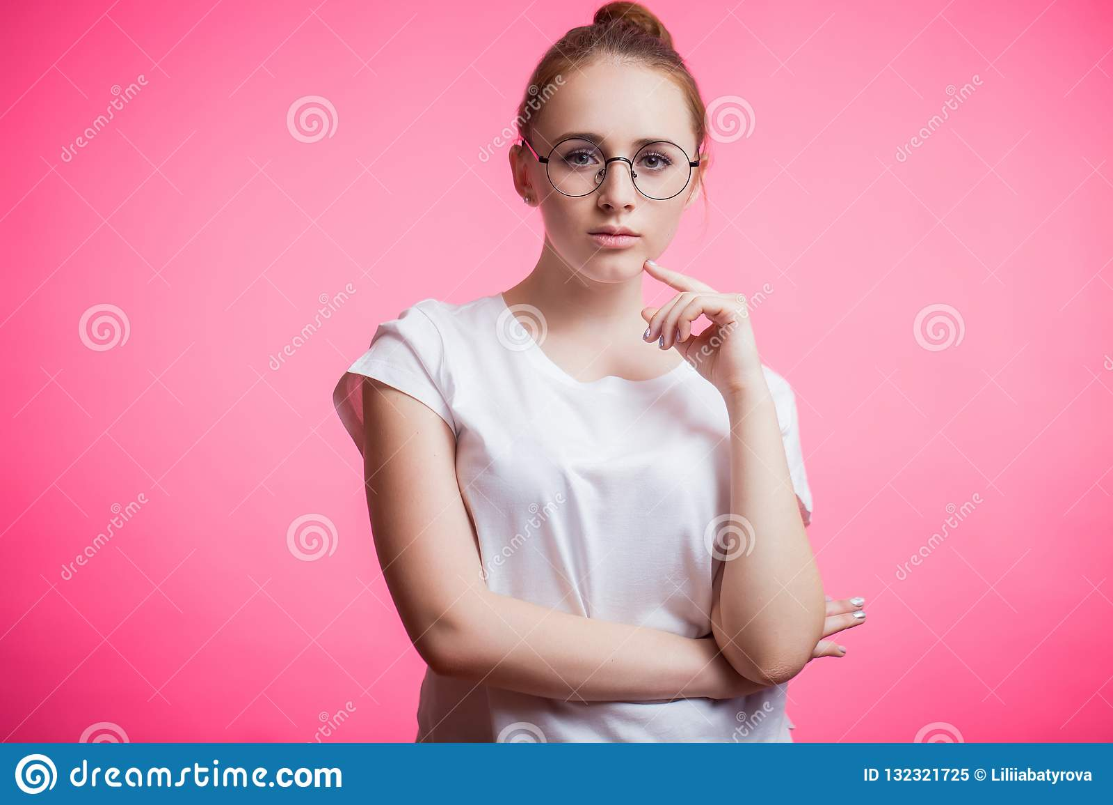 Horisontalstående av en härlig ung kvinna som bär runda exponeringsglas, en vit skjorta och ser kameran på en rosa bakgrund