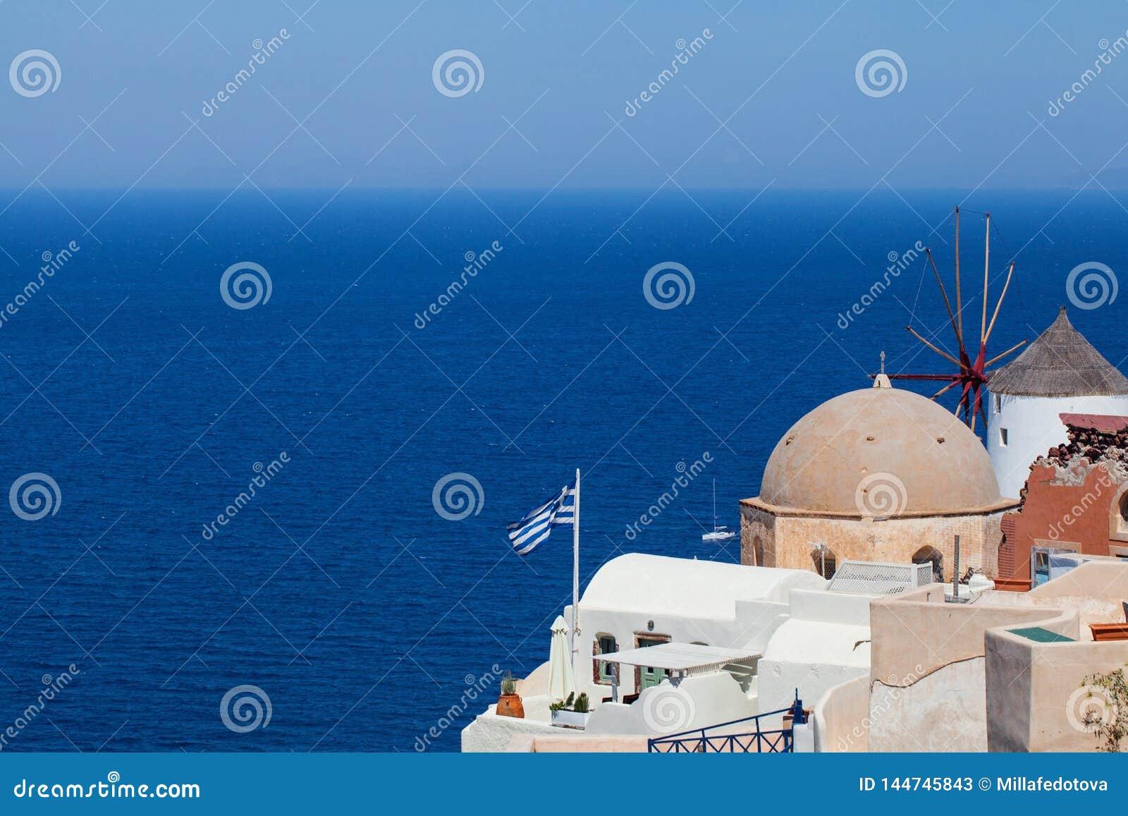 Horizon de Santorini avec le drapeau grec, la mer, le ciel bleu et la ville Point de rep