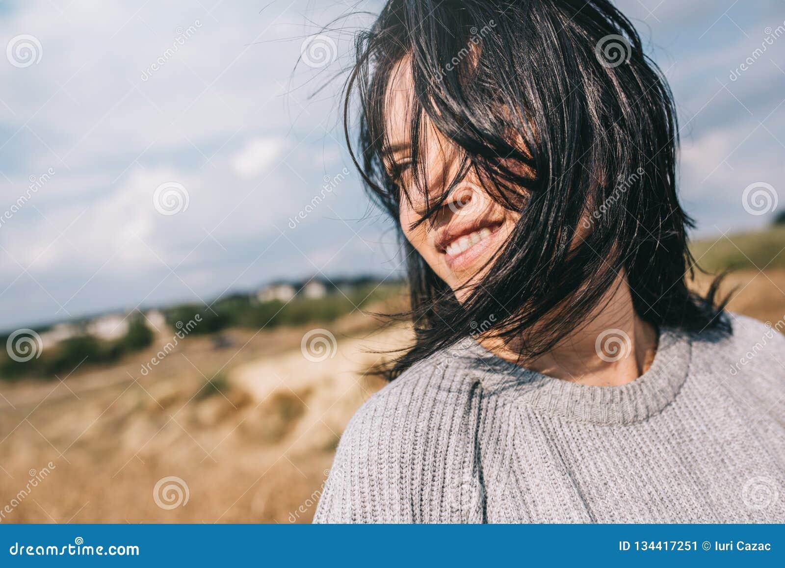 Horizontaal bebouwd portret van mooie glimlachende vrouw die sweater dragen die speels met winderig haar en het onbezorgde stelle