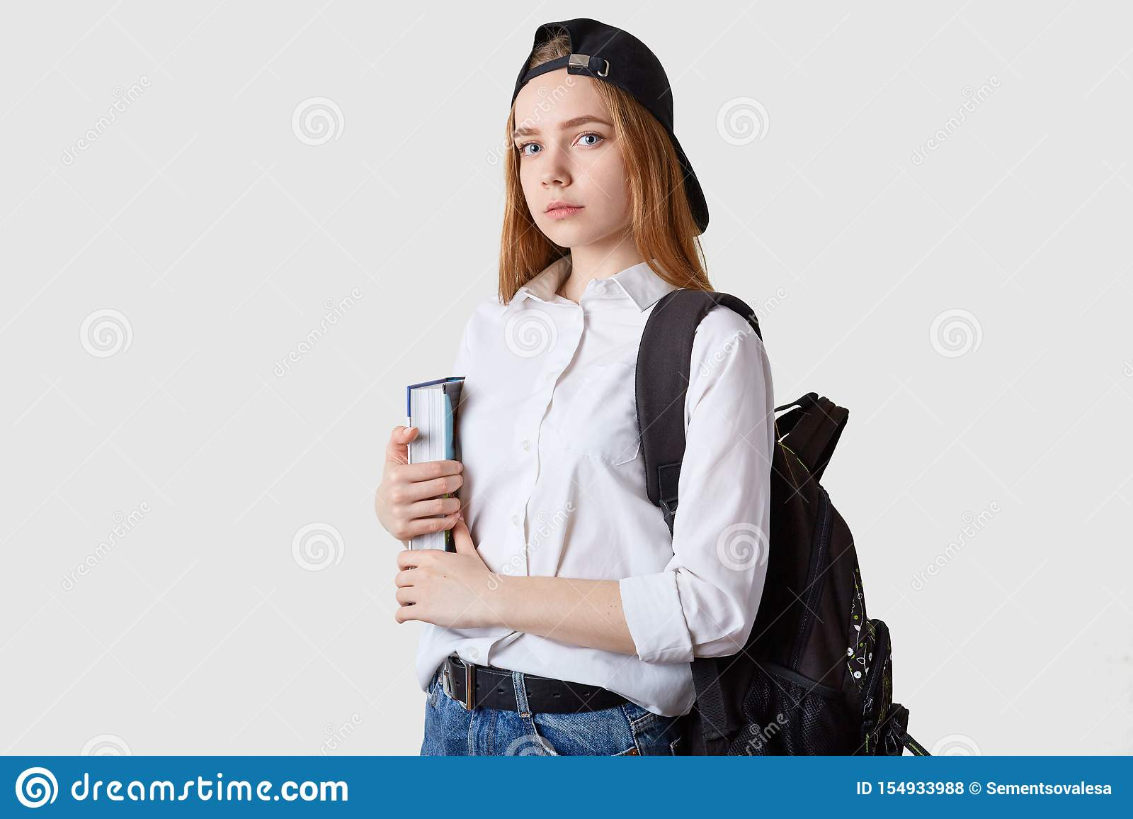 Horizontaal schot van studentenmeisje status geïsoleerd over witte achtergrond, die document omslagen in handen houden, die blous