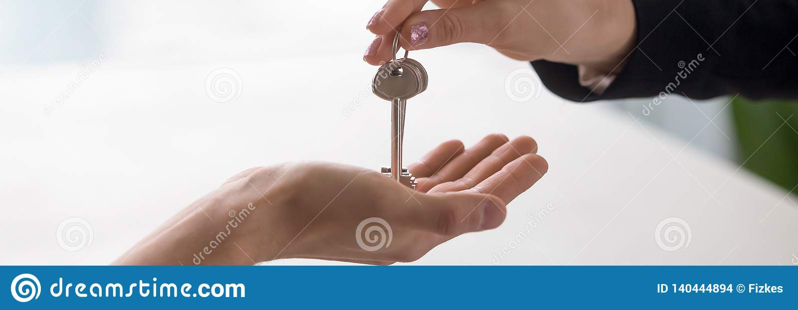 Closeup hands real estate agent giving keys to home owner