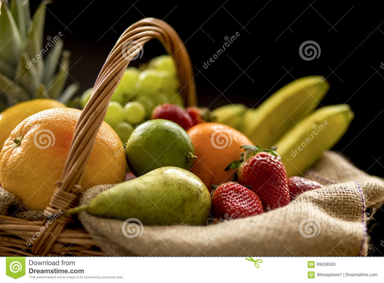 Horizontal Closeup detail on a basket full of fruit on a dark background