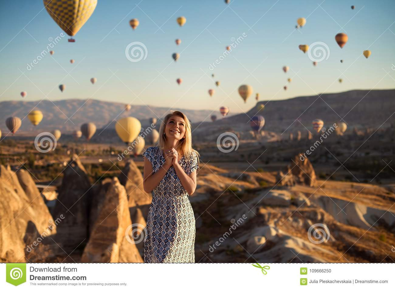 Horizontal outdoor shot of happy blonde young smiling woman in dress being excited as stands on high mountain looks