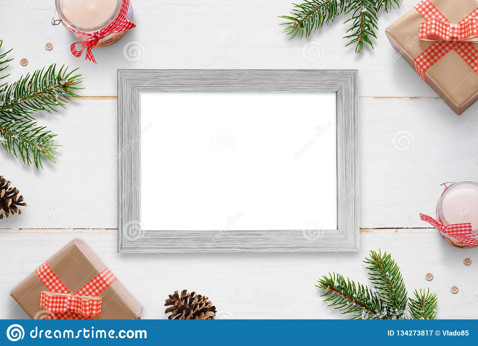 Horizontal photo frame surrounded with Christmas New Year gifts, tree branches and decorations.