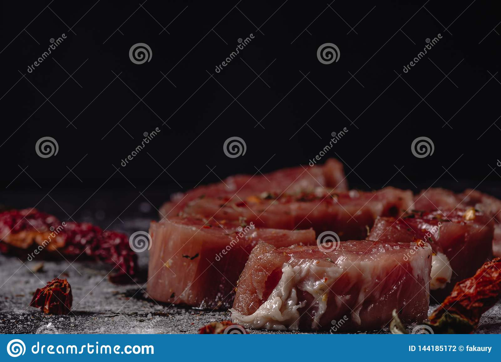 Horizontal photo of raw pork tenderloin meat. Raw meat is on rustic dark baton board, with pepper and salt